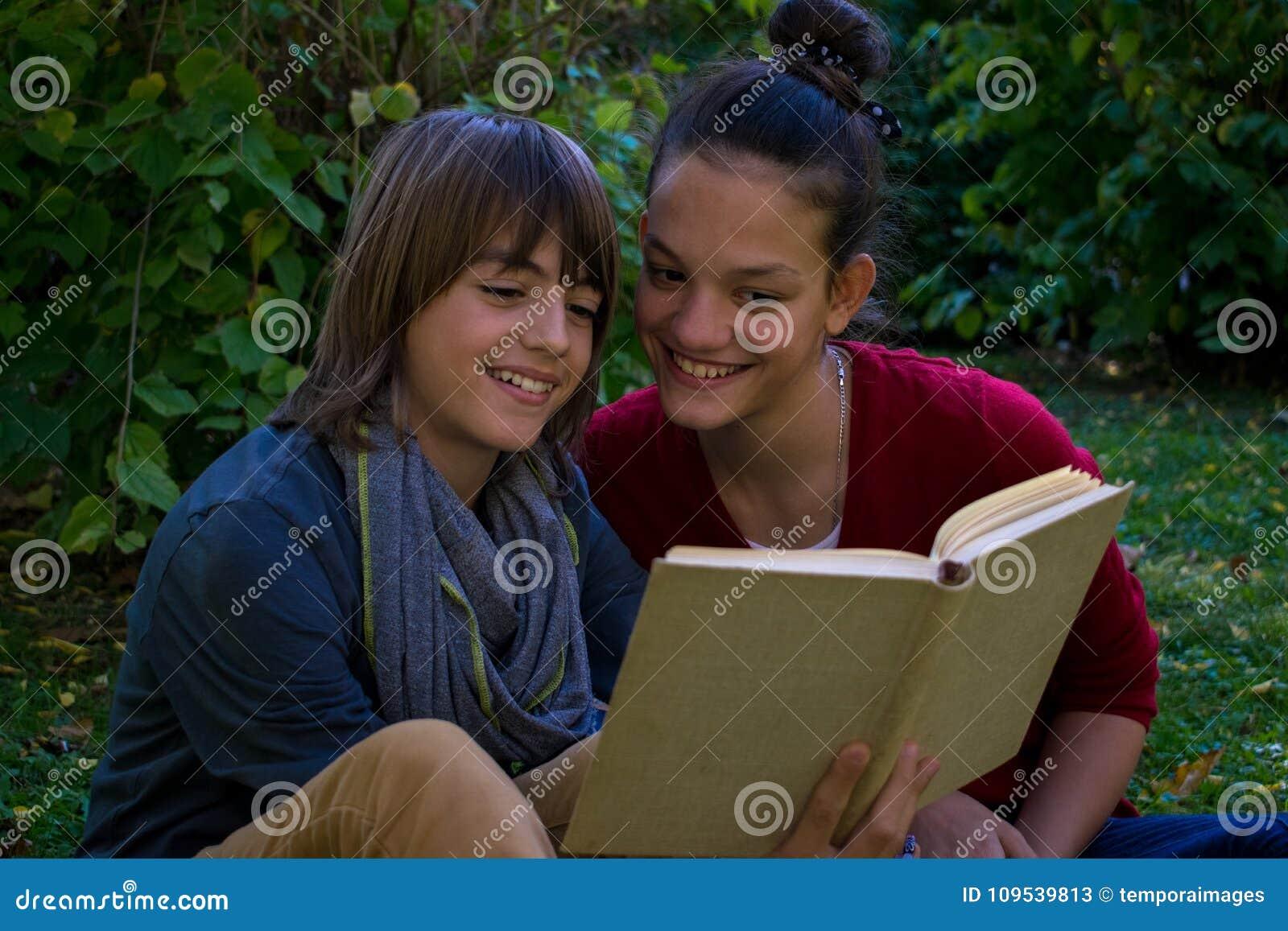 Ευτυχείς έφηβοι που διαβάζουν ένα βιβλίο στο πάρκο
