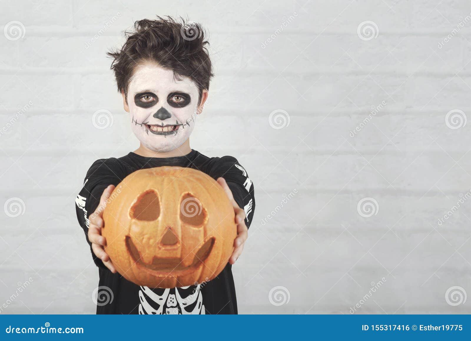 Ευτυχείς αποκριές αστείο παιδί σε ένα κοστούμι σκελετών με την κολοκύθα αποκριών