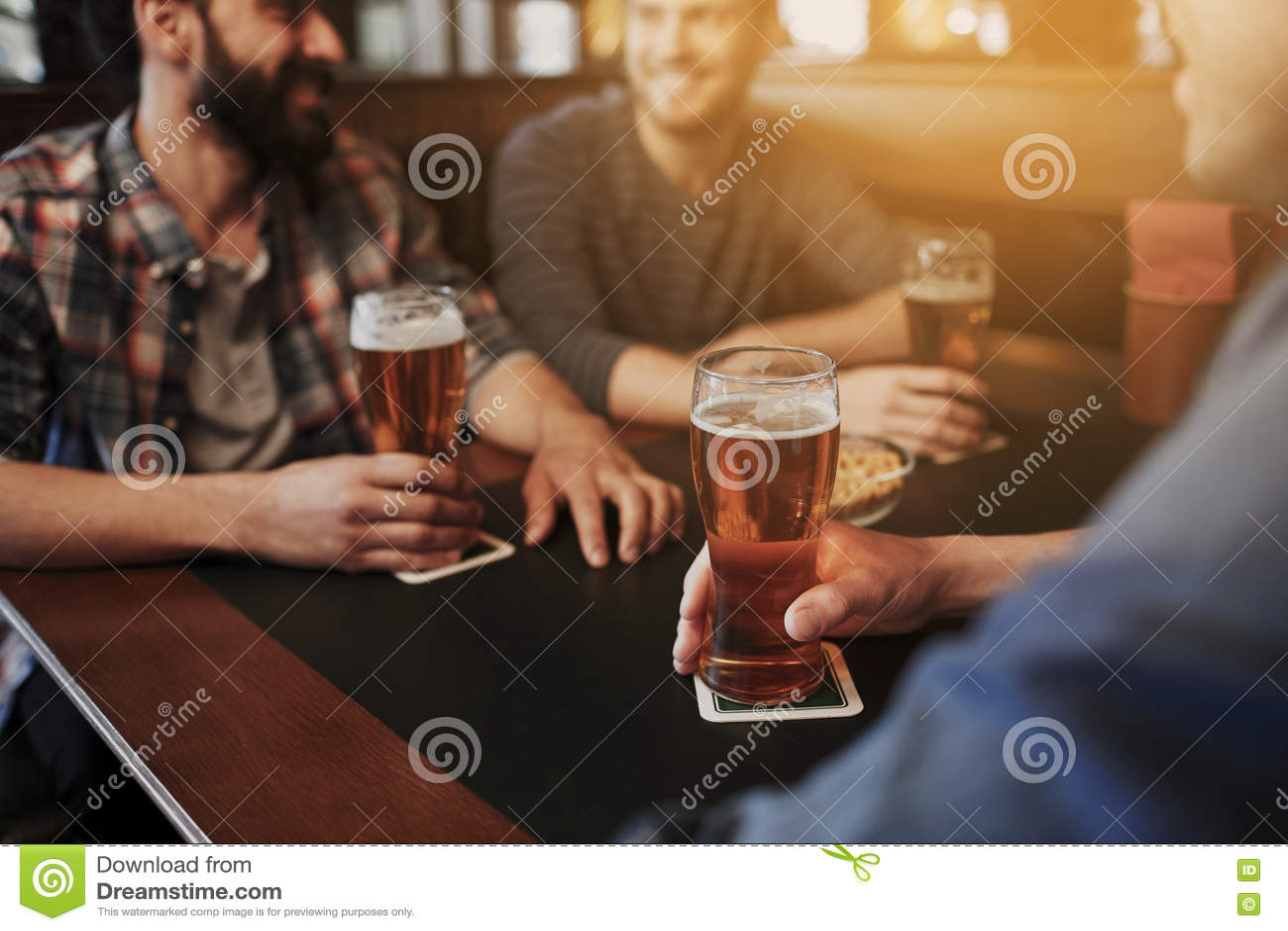 Ευτυχείς αρσενικοί φίλοι που πίνουν την μπύρα στο φραγμό ή το μπαρ