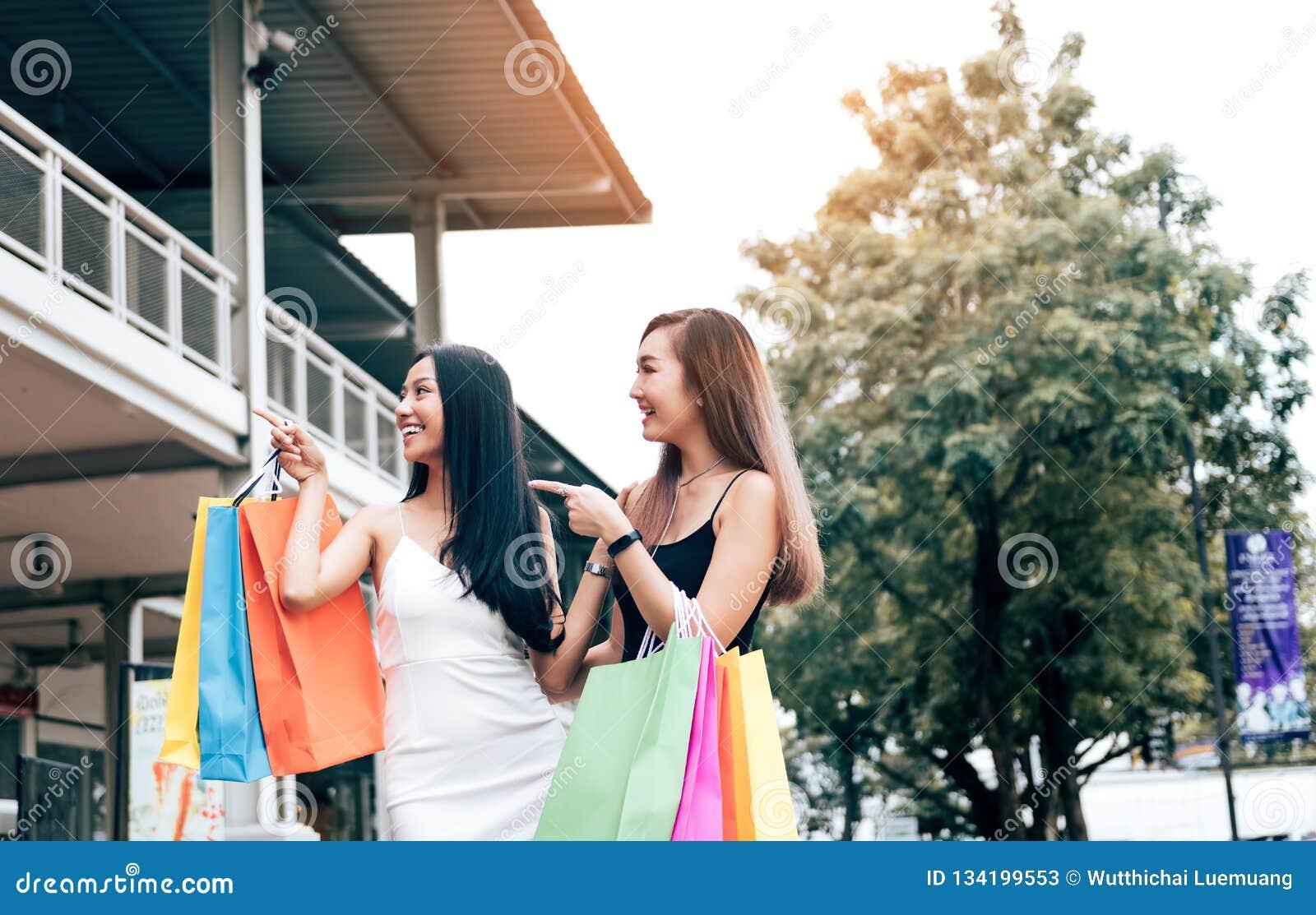 Ευτυχείς ασιατικοί φίλοι που περπατούν στη λεωφόρο με να κάνει που ψωνίζει από κοινού