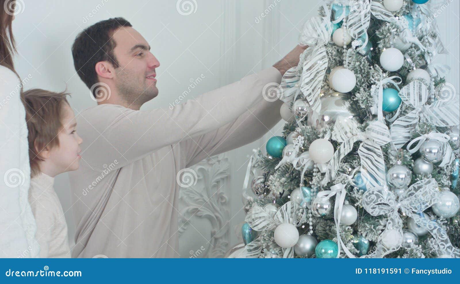 Ευτυχείς γονείς και ο γιος τους που διακοσμούν το χριστουγεννιάτικο δέντρο στο καθιστικό