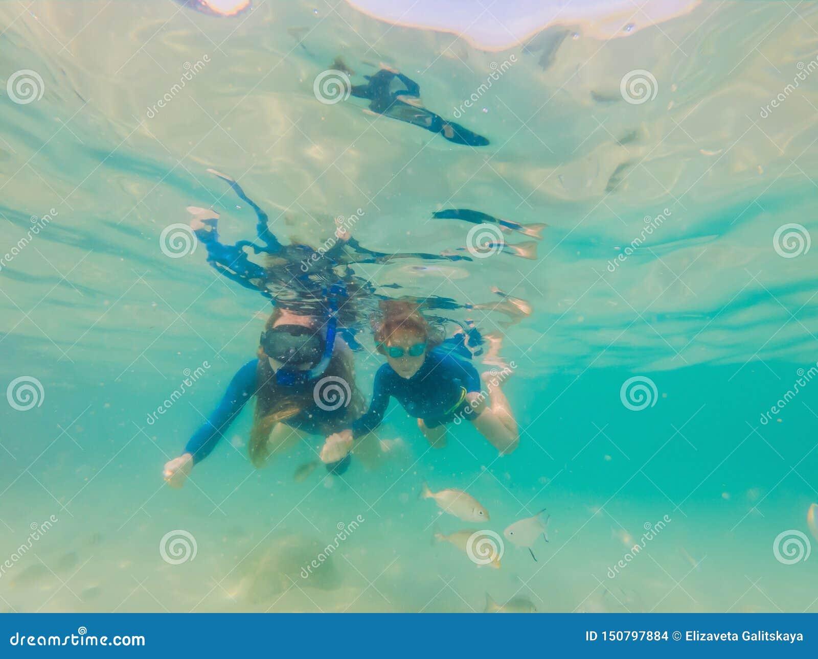 Ευτυχείς μητέρα και γιος που κολυμπούν με αναπνευτήρα στη θάλασσα Εξετάστε τα ψάρια κάτω από το νερό
