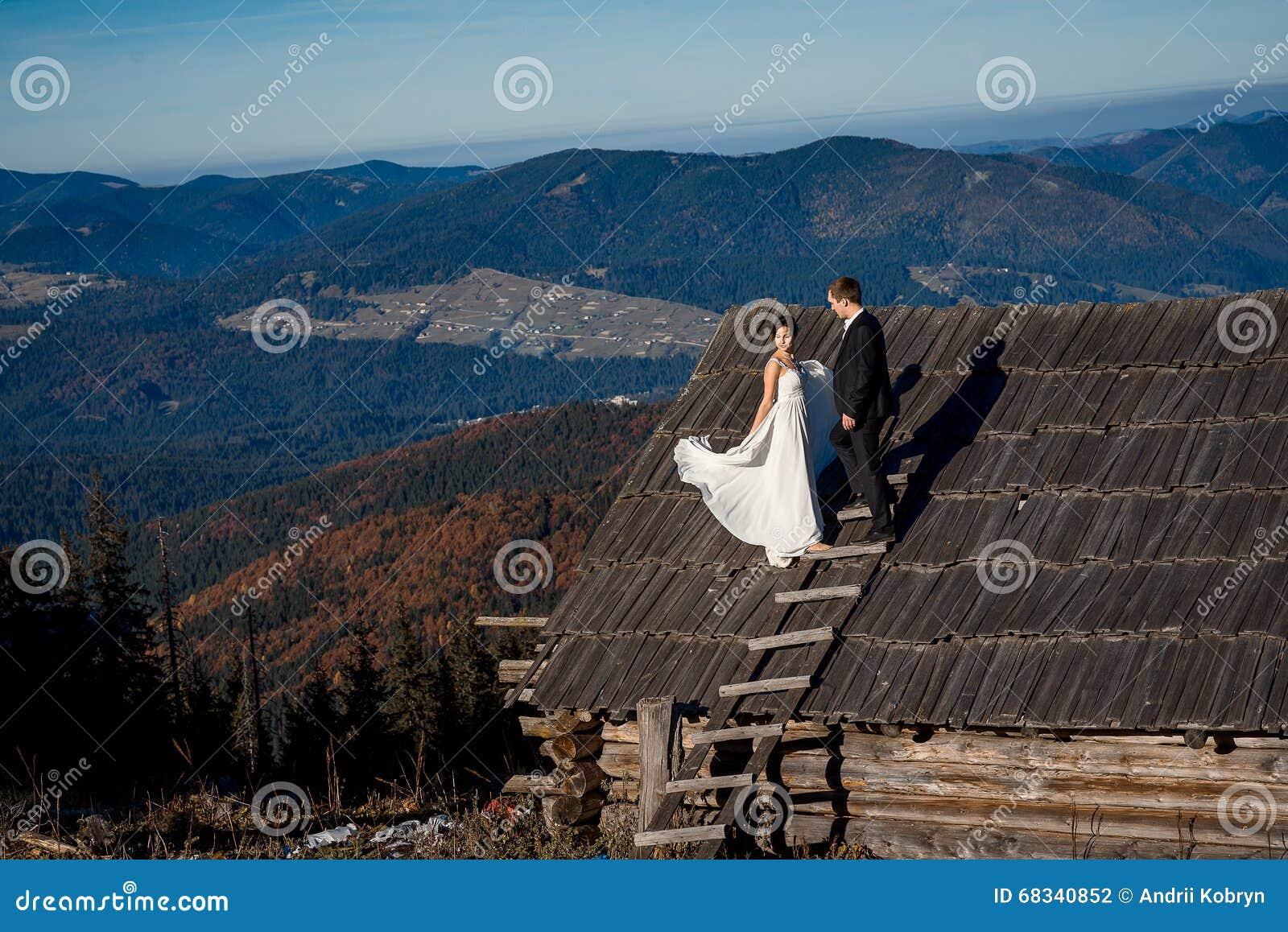 Ευτυχείς νύφη και νεόνυμφος στη στέγη του εξοχικού σπιτιού Συναρπαστικό υπόβαθρο τοπίων βουνών