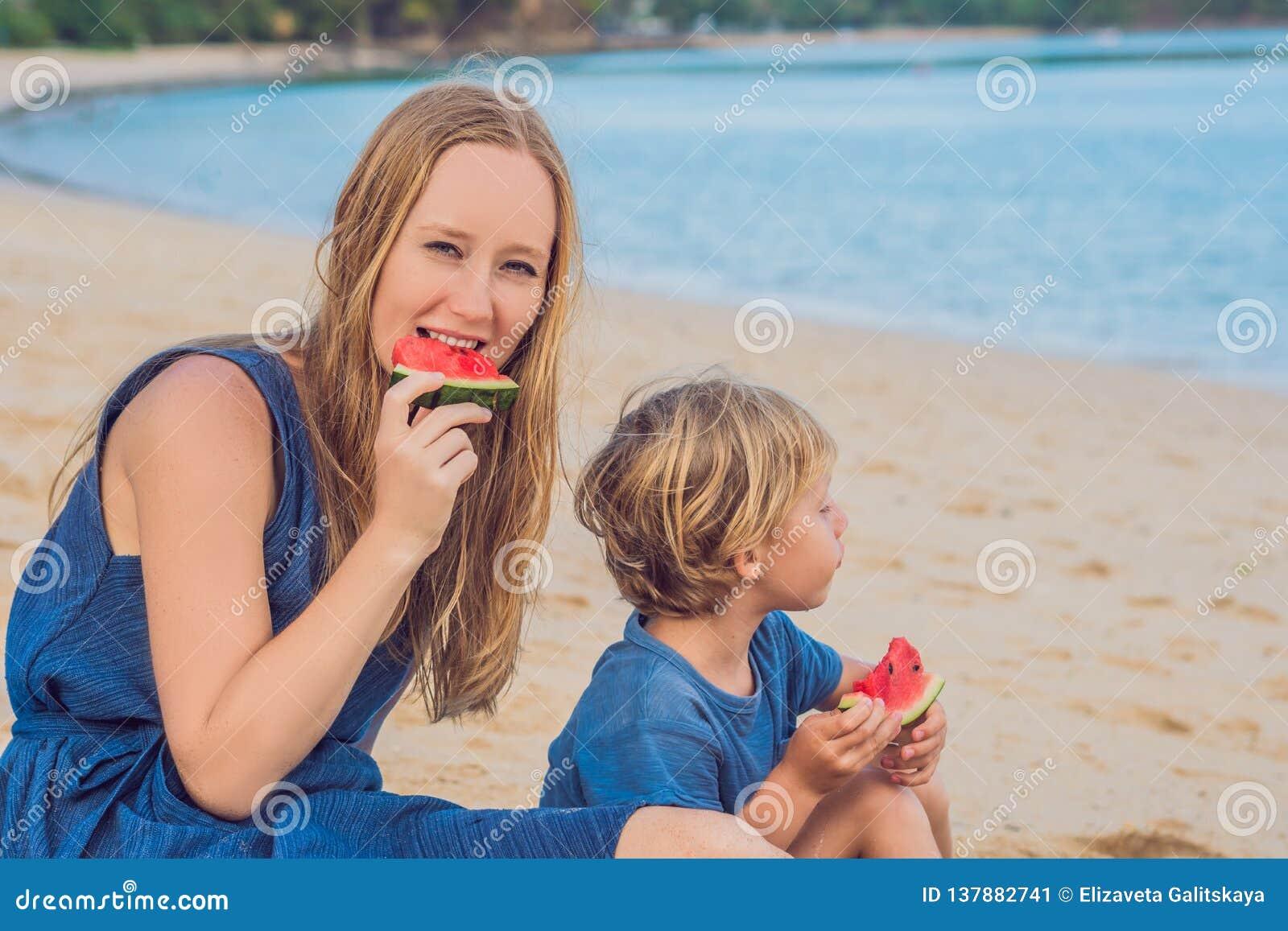 Ευτυχείς οικογενειακοί μητέρα και γιος που τρώνε ένα καρπούζι στην παραλία Τα παιδιά τρώνε τα υγιή τρόφιμα