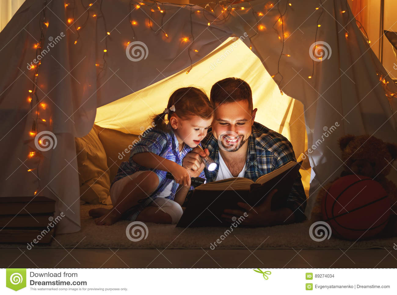 Ευτυχείς οικογενειακός πατέρας και κόρη παιδιών που διαβάζει ένα βιβλίο στη σκηνή