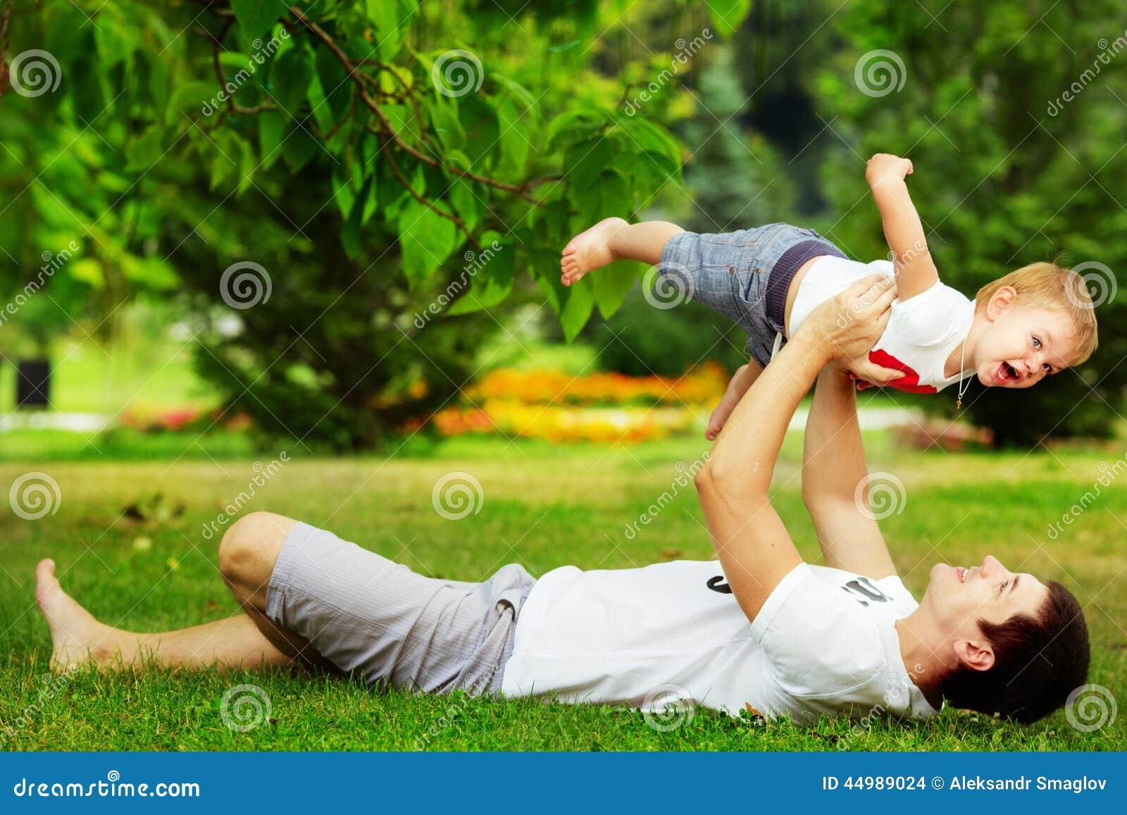 Ευτυχείς πατέρας και γιος που παίζουν μαζί να έχε τη διασκέδαση στο πράσινο SU