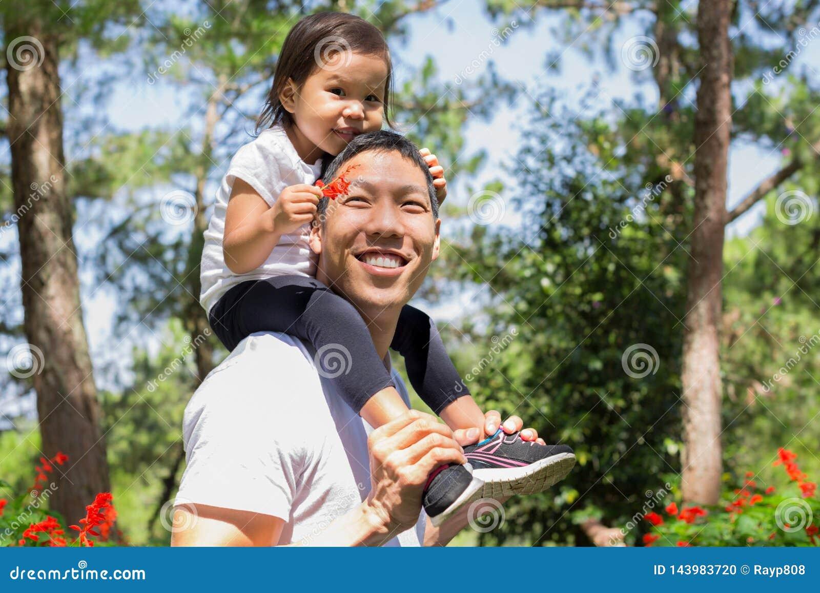Ευτυχείς πατέρας και παιδί που γελούν και που παίζουν μαζί, φροντίζοντας κόρη στην πλάτη του σε ένα υπαίθριο δασικό πάρκο