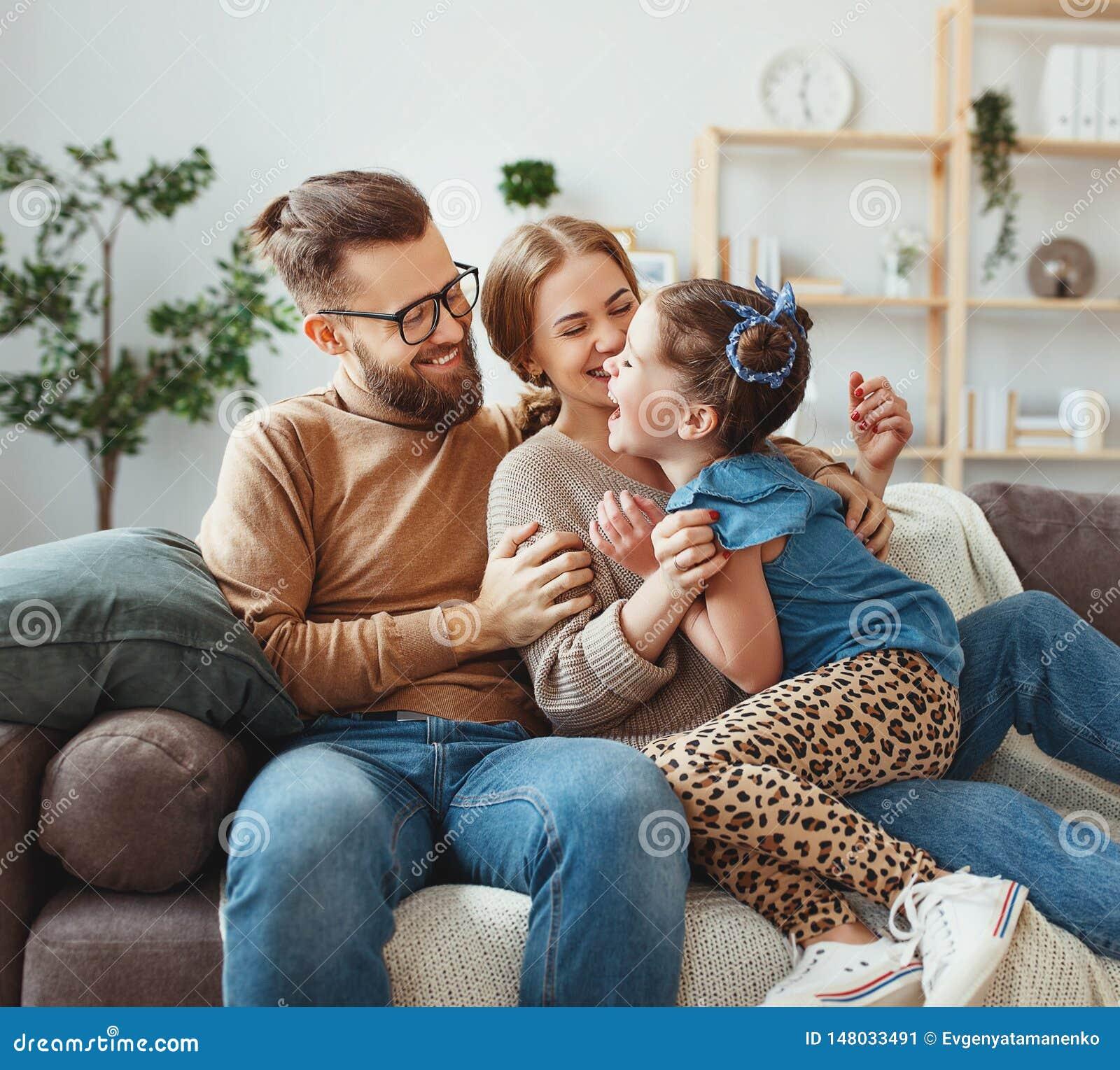 Ευτυχείς πατέρας οικογενειακών μητέρων και κόρη παιδιών που γελά στο σπίτι