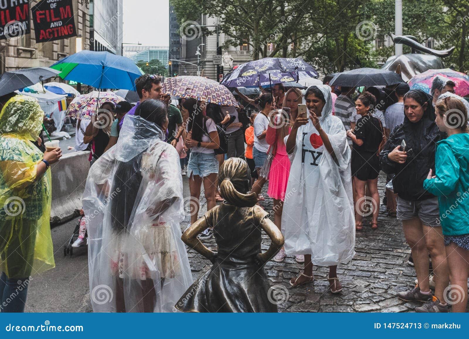 Ευτυχείς τουρίστες που παίρνουν τις φωτογραφίες με το άφοβο άγαλμα κοριτσιών στο χαμηλότερο Μανχάταν, σε μια βροχερή ημέρα