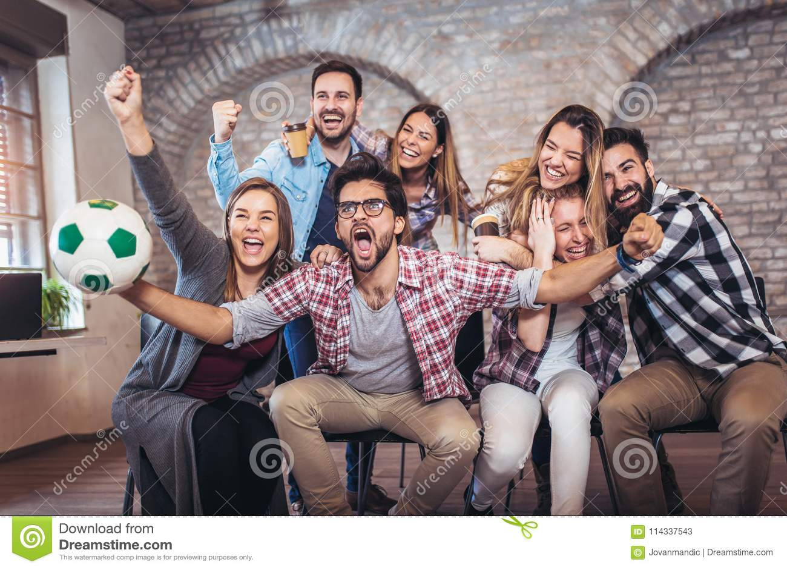 Ευτυχείς φίλοι ή οπαδοί ποδοσφαίρου που προσέχουν το ποδόσφαιρο στη TV και που γιορτάζουν τη νίκη