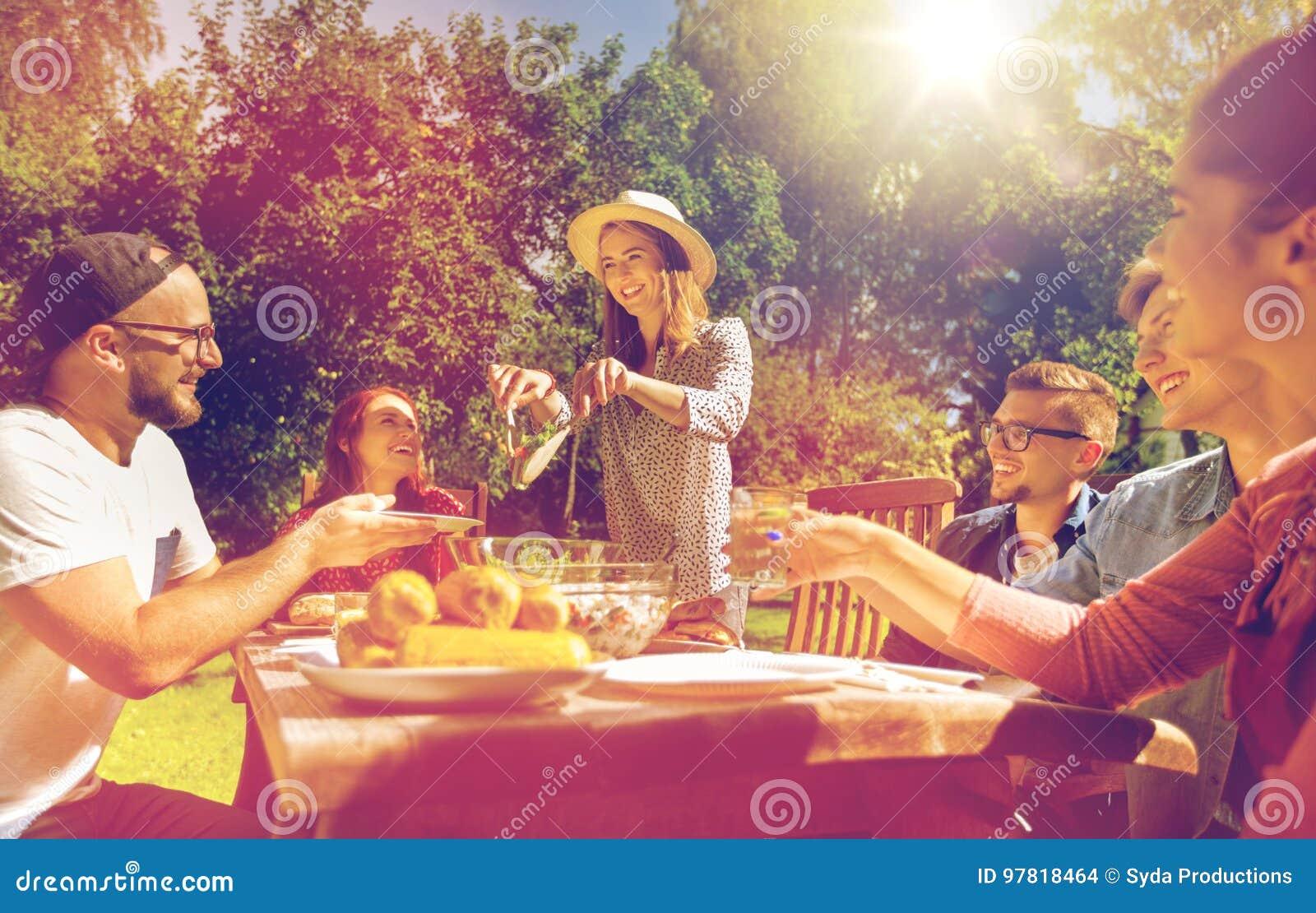 Ευτυχείς φίλοι που έχουν το γεύμα στο κόμμα θερινών κήπων