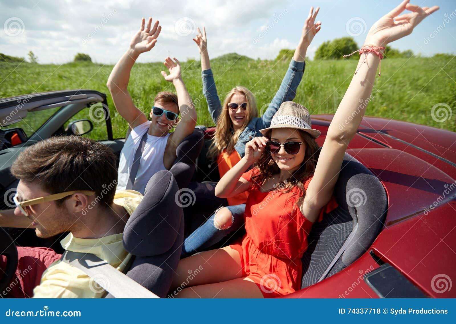 Ευτυχείς φίλοι που οδηγούν στο αυτοκίνητο καμπριολέ στη χώρα