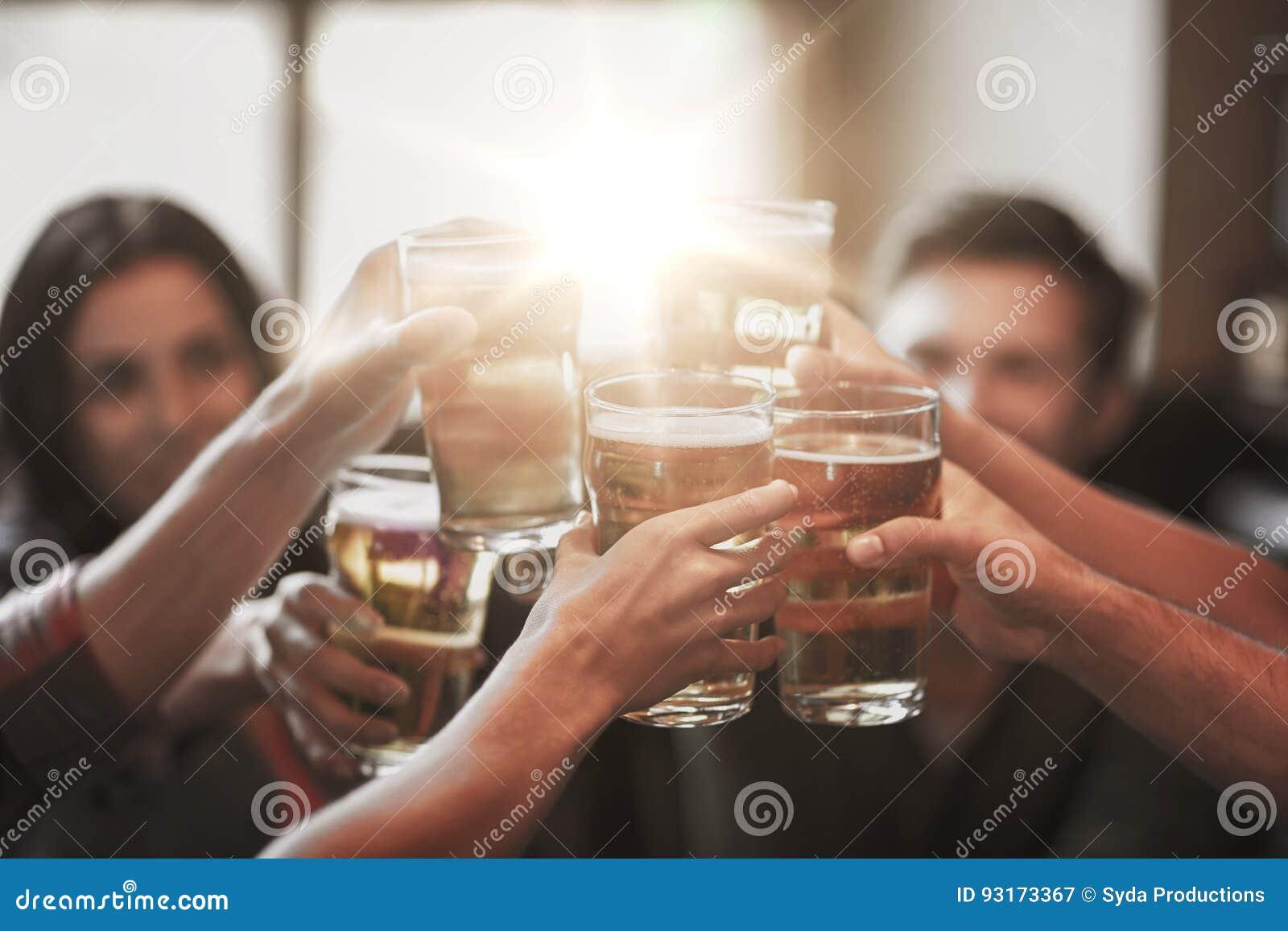 Ευτυχείς φίλοι που πίνουν την μπύρα στο φραγμό ή το μπαρ