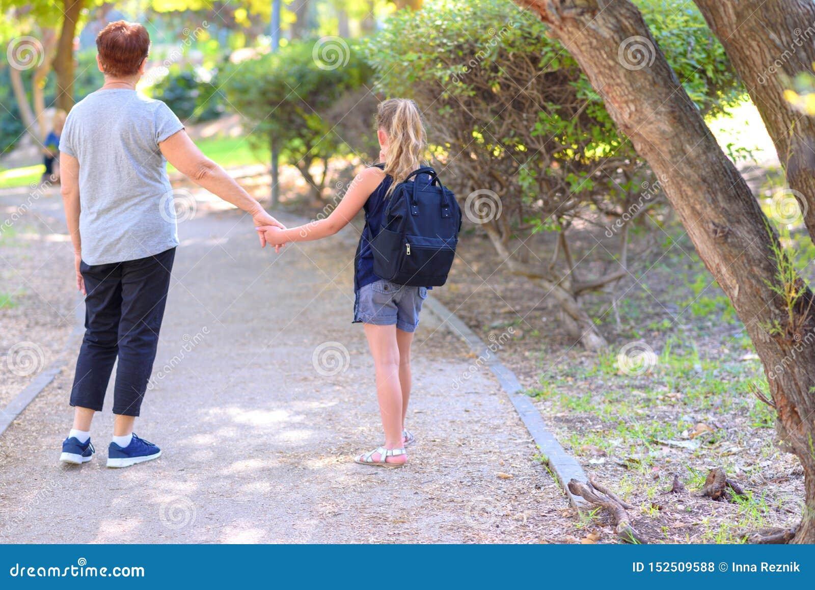 Ευτυχείς Grandma και εγγονή που περπατούν στο σχολείο στην οδό στο πάρκο φθινοπώρου