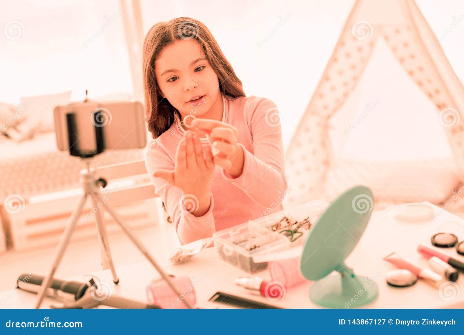 Ευχάριστο νέο κορίτσι που κρατά ένα χρυσό δαχτυλίδι