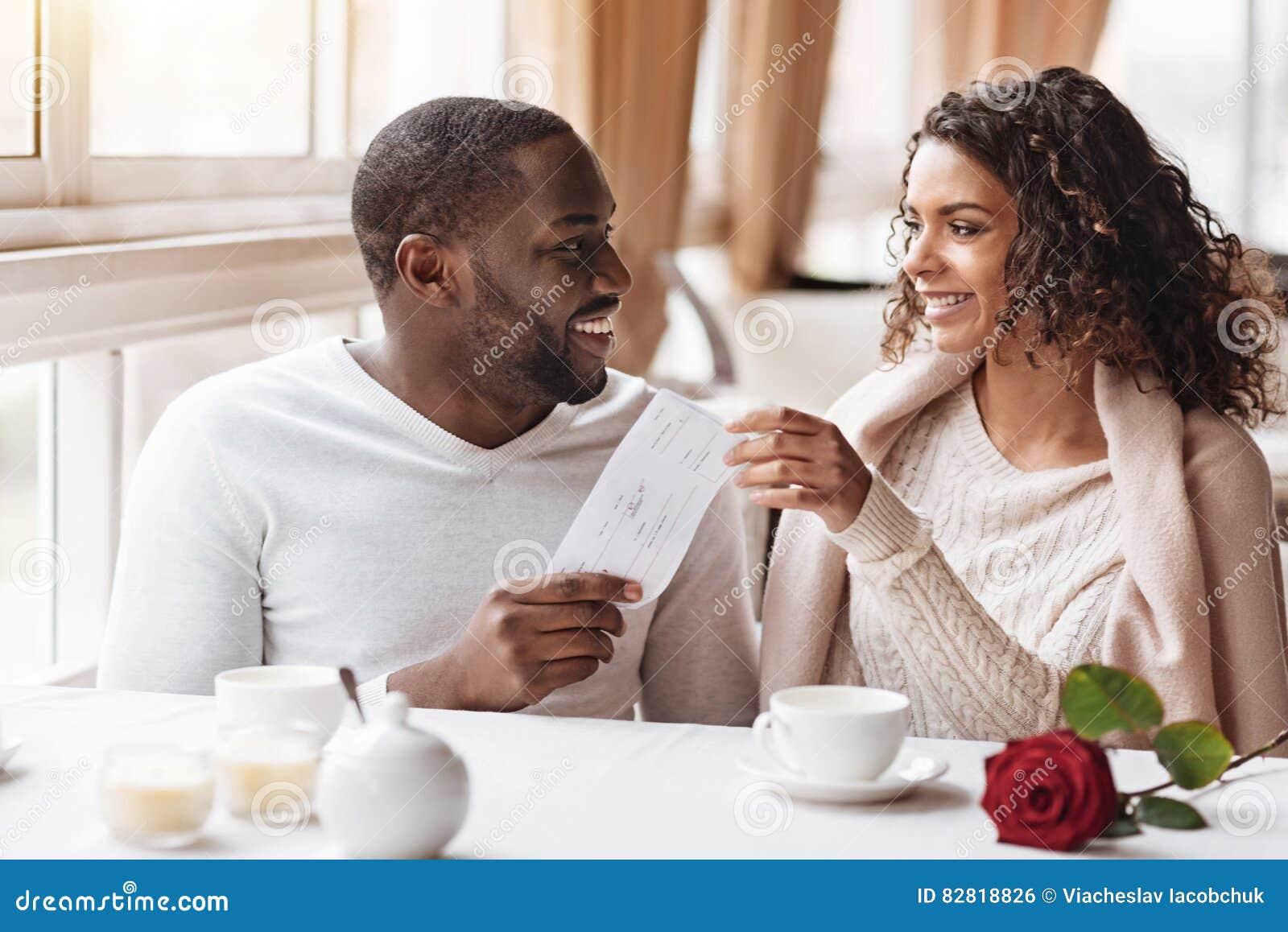 Ευχαριστημένος άνδρας αφροαμερικάνων που δίνει ένα παρόν στη γυναίκα