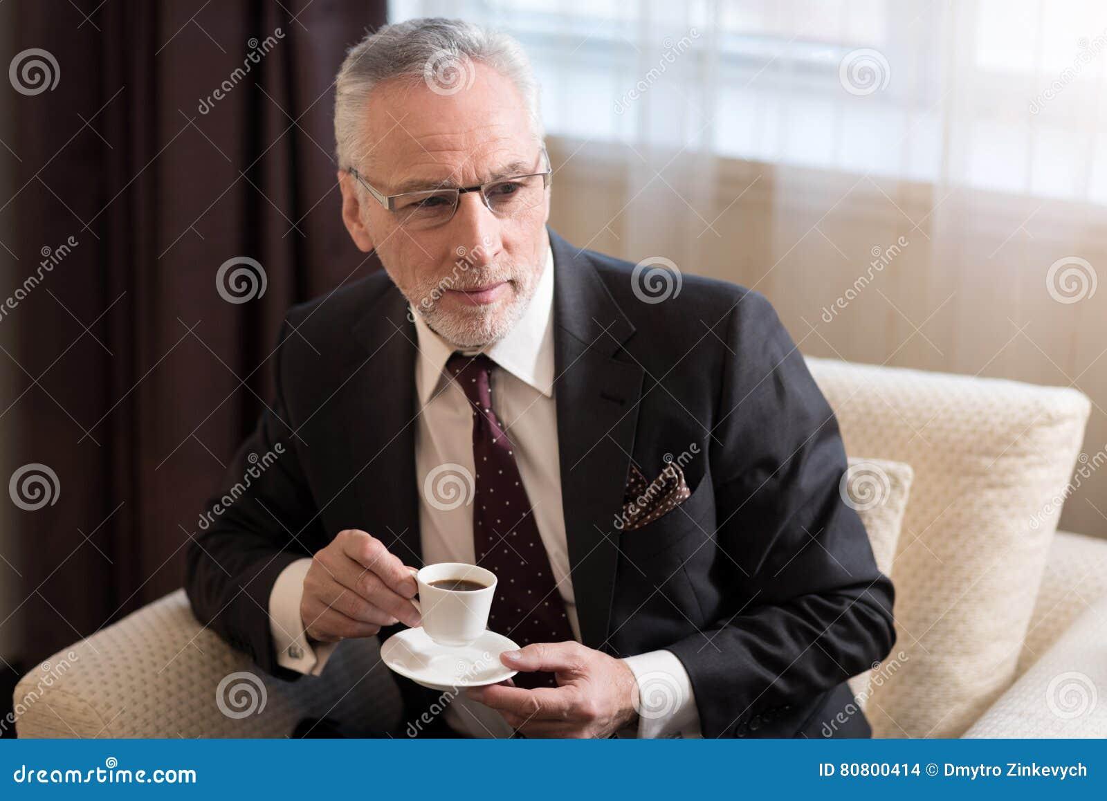 Ευχαριστημένος γενειοφόρος καφές κατανάλωσης επιχειρηματιών στο ξενοδοχείο