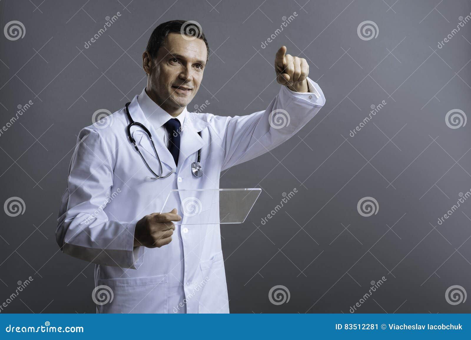 Ευχαριστημένος γιατρός που δείχνει κάπου με το δάχτυλό του