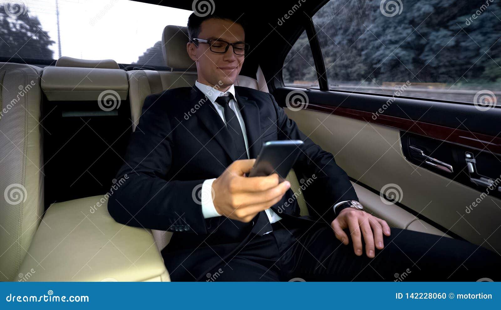 Ευχαριστημένος επιχειρηματίας που οδηγά στο backseat του ακριβού αυτοκινήτου, που χρησιμοποιεί το τηλέφωνο app