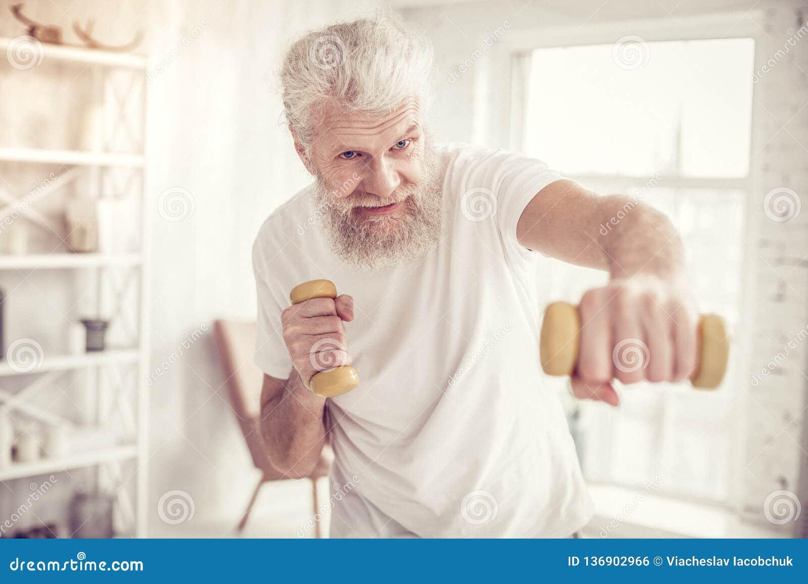 Ευχαριστημένος ηλικίας αθλητικός τύπος που ανυψώνει τους κίτρινους αλτήρες ενεργά
