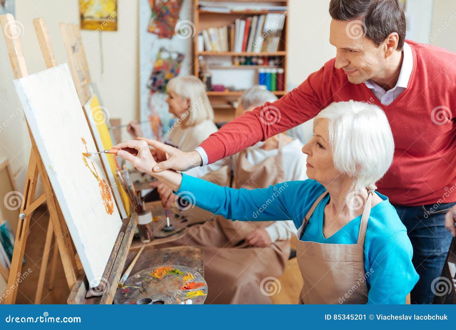 Ευχαριστημένος καλλιτέχνης που βοηθά την ηλικιωμένη γυναίκα στη ζωγραφική του στούντιο