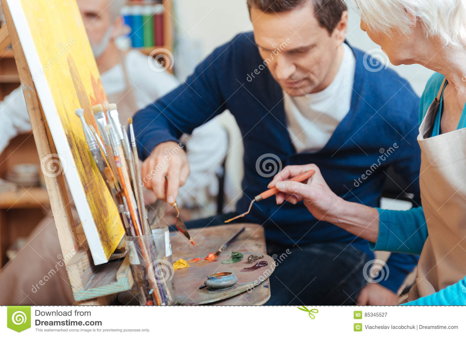 Ευχαριστημένος καλλιτέχνης που βοηθά την ηλικιωμένη γυναίκα στη ζωγραφική
