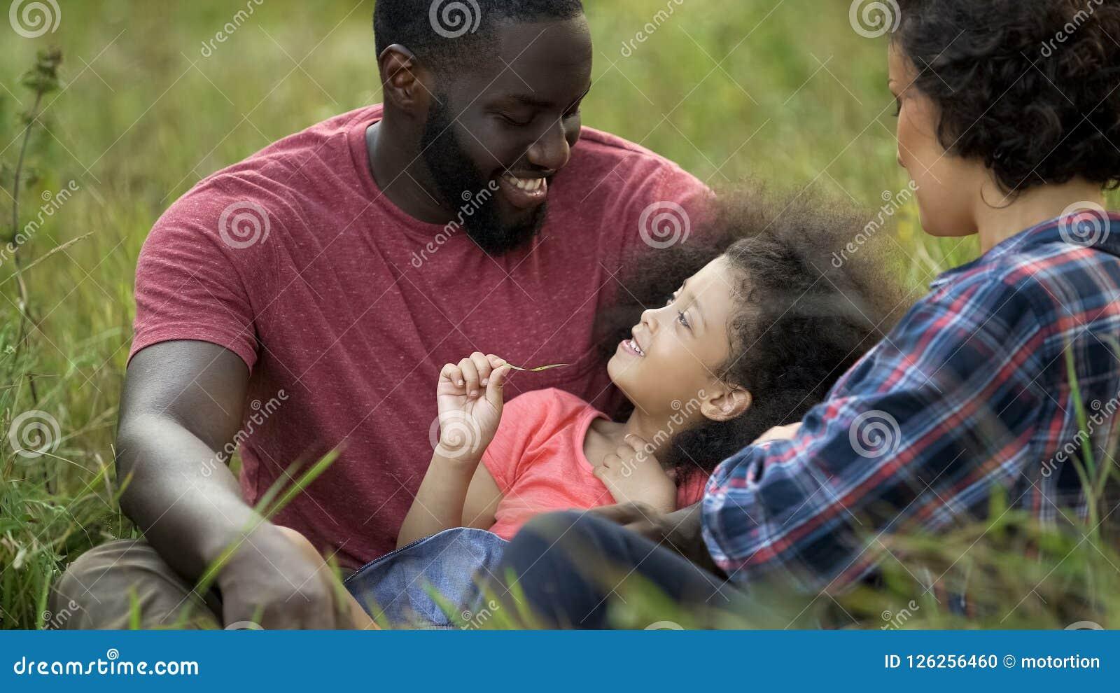 Ευχαριστημένος πατέρας που κρατά λίγη κόρη και που παίζει με τη σγουρή τρίχα της, προσοχή