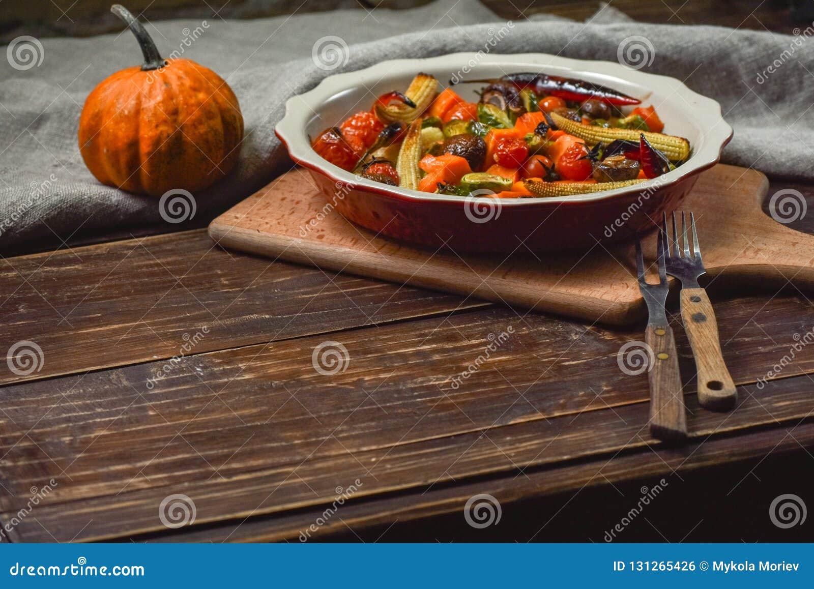 Εύγευστα λαχανικά που ψήνονται στο φούρνο σε ένα κεραμικό πιάτο σε έναν ξύλινο πίνακα Συσκευές, ύφασμα και εξαρτήματα διάστημα αν