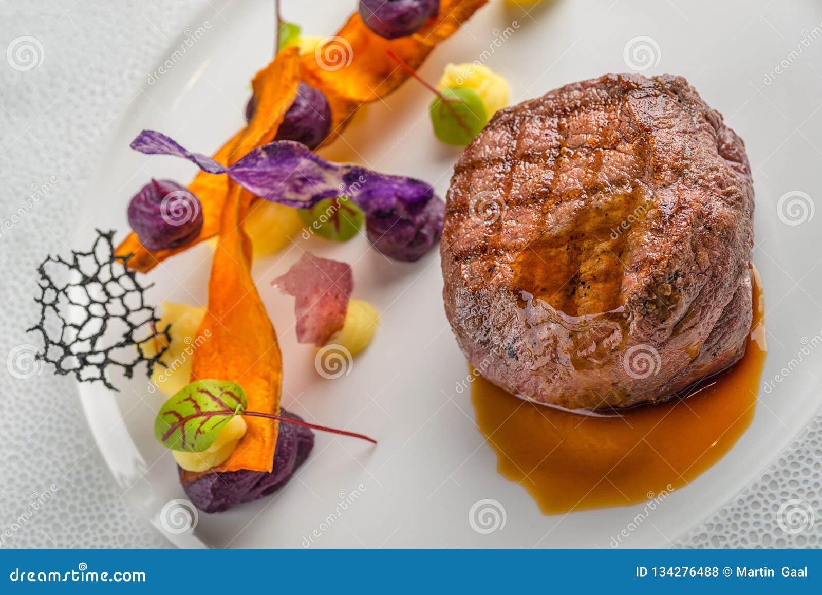 Εύγευστη μπριζόλα βόειου κρέατος με τη σάλτσα και το λαχανικό, που εξυπηρετούνται στο άσπρο πιάτο, τη σύγχρονη γαστρονομία, εστια
