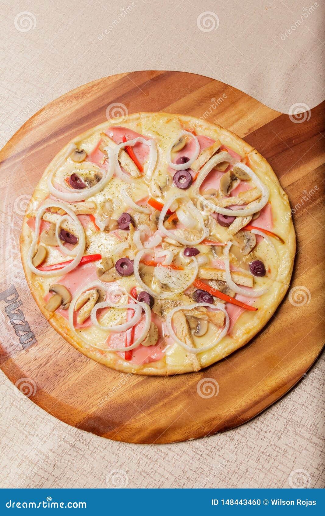 Εύγευστη πίτσα που εξυπηρετείται στο ξύλινο πιάτο - Imagen