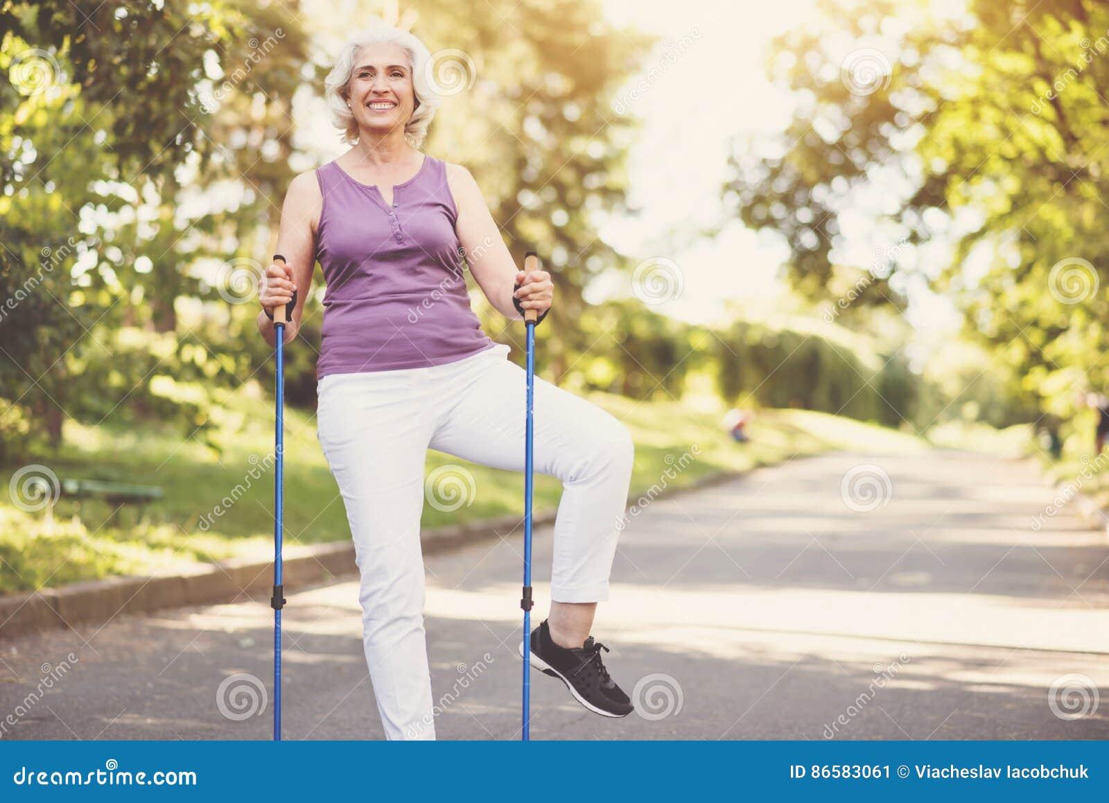 Εύθυμη ανώτερη γυναίκα που κάνει μια σωματική άσκηση