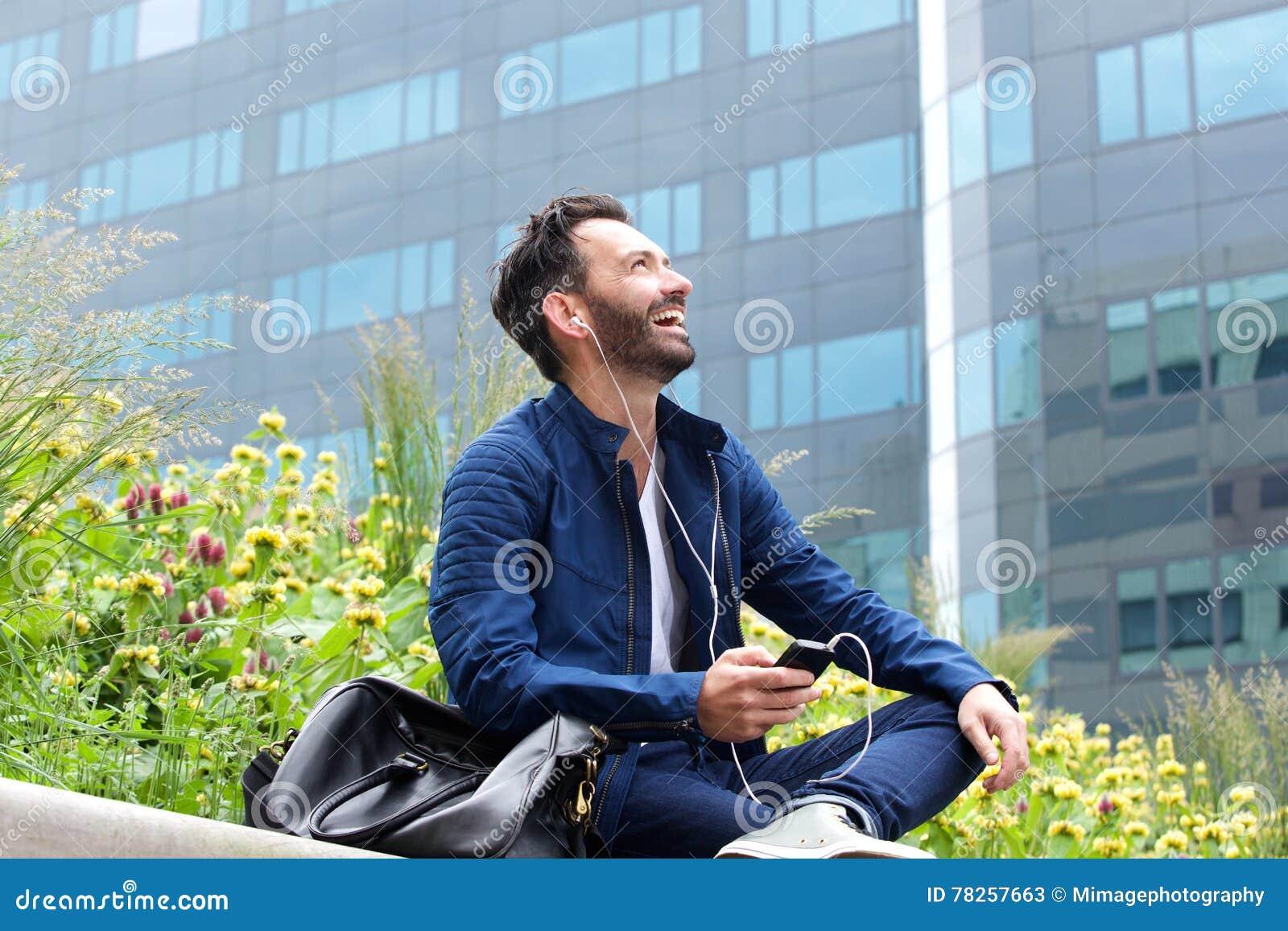 Εύθυμη απόλαυση ατόμων που ακούει τη μουσική στο κινητό τηλέφωνο