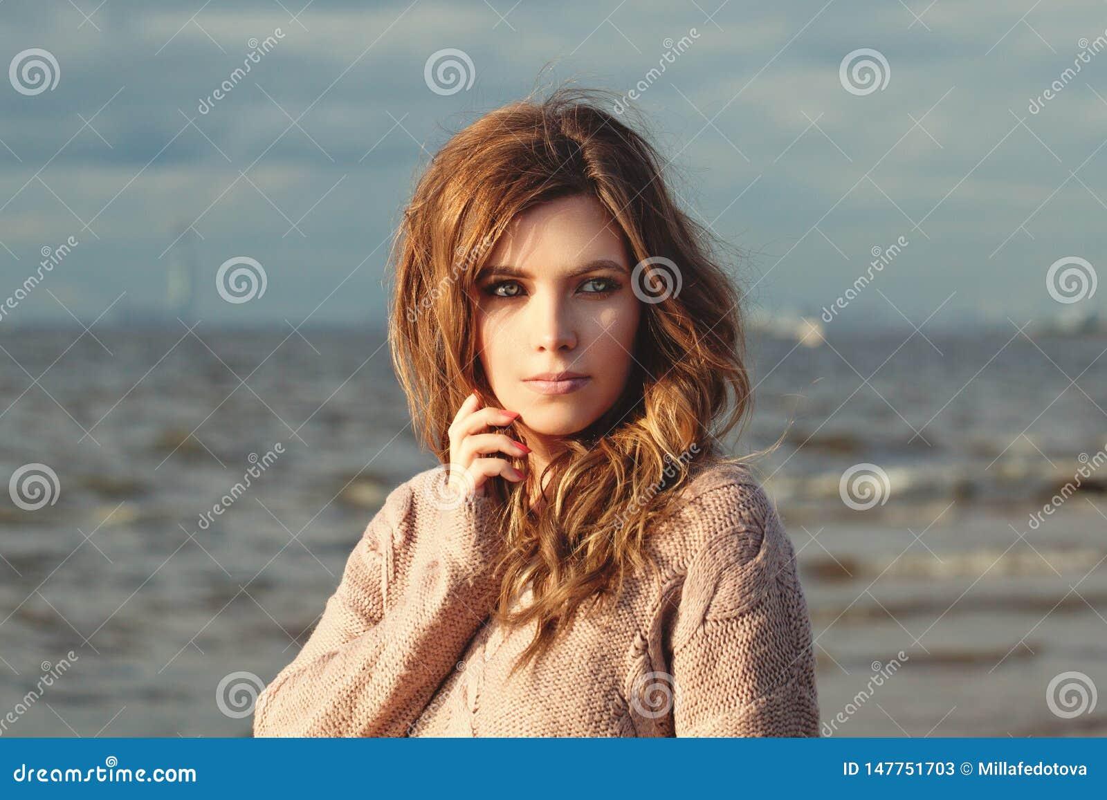 Εύθυμη γυναίκα στην ωκεάνια ακτή την ηλιόλουστη ημέρα