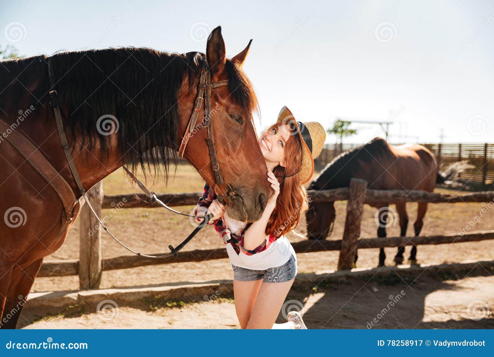 Εύθυμη γυναίκα cowgirl με το άλογό της στο αγρόκτημα