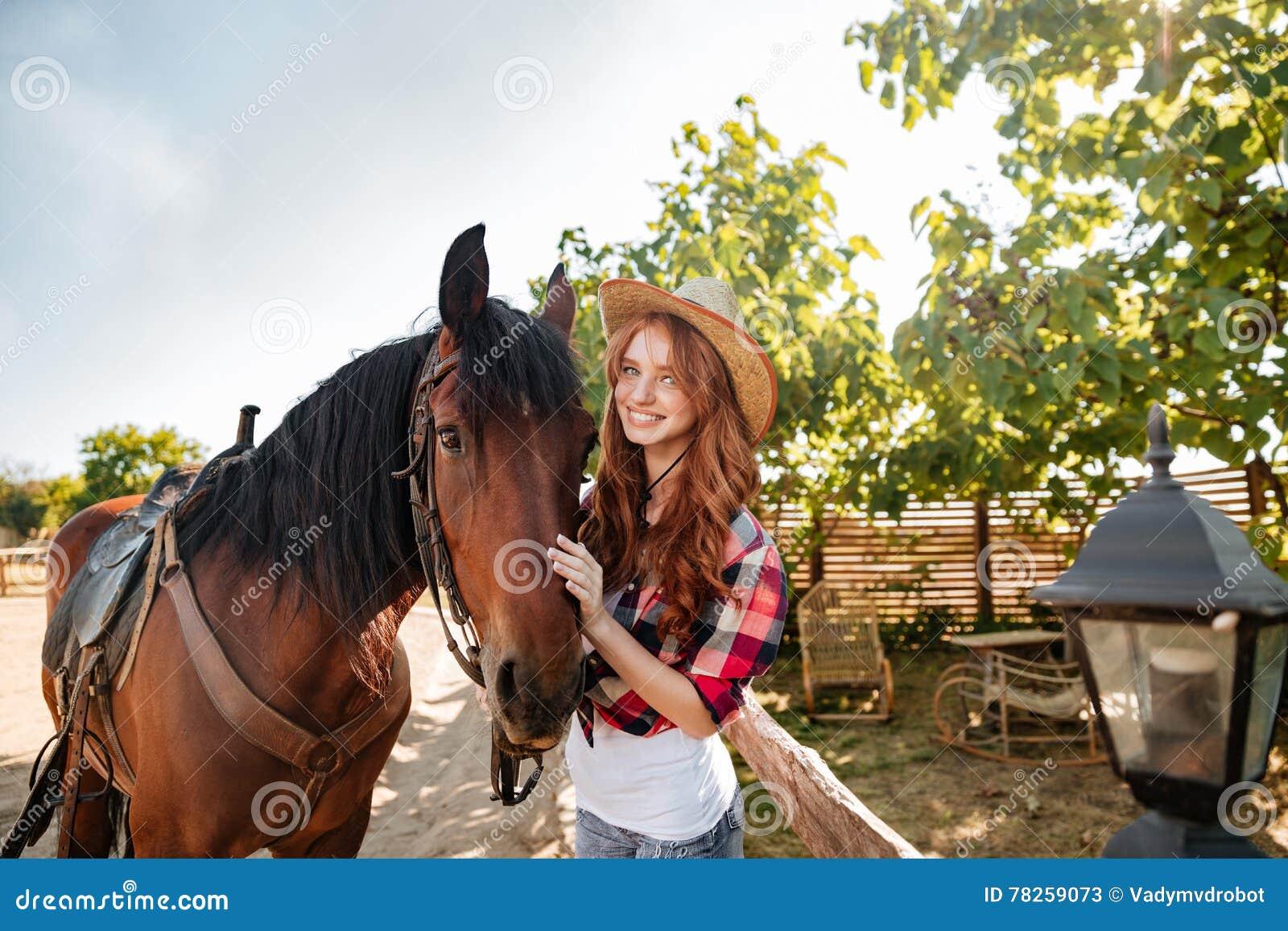 Εύθυμη γυναίκα cowgirl που στέκεται με το άλογό της στο χωριό