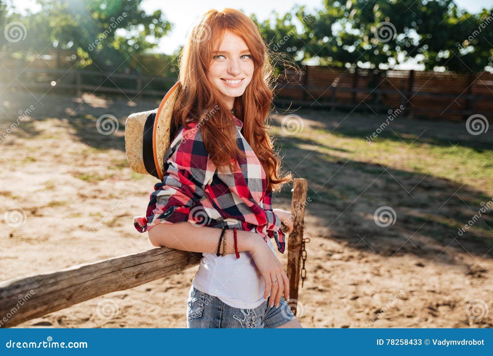 Εύθυμη γυναίκα cowgirl που στέκεται στο χωριό