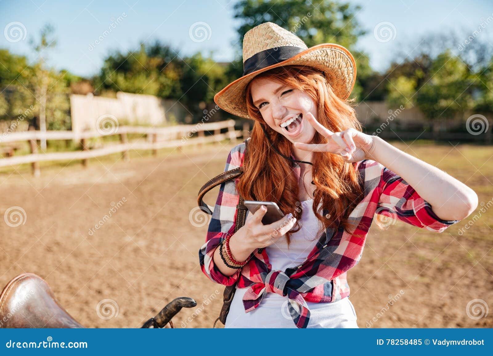 Εύθυμη γυναίκα cowgirl που χρησιμοποιεί το τηλέφωνο κυττάρων και που παρουσιάζει σημάδι ειρήνης