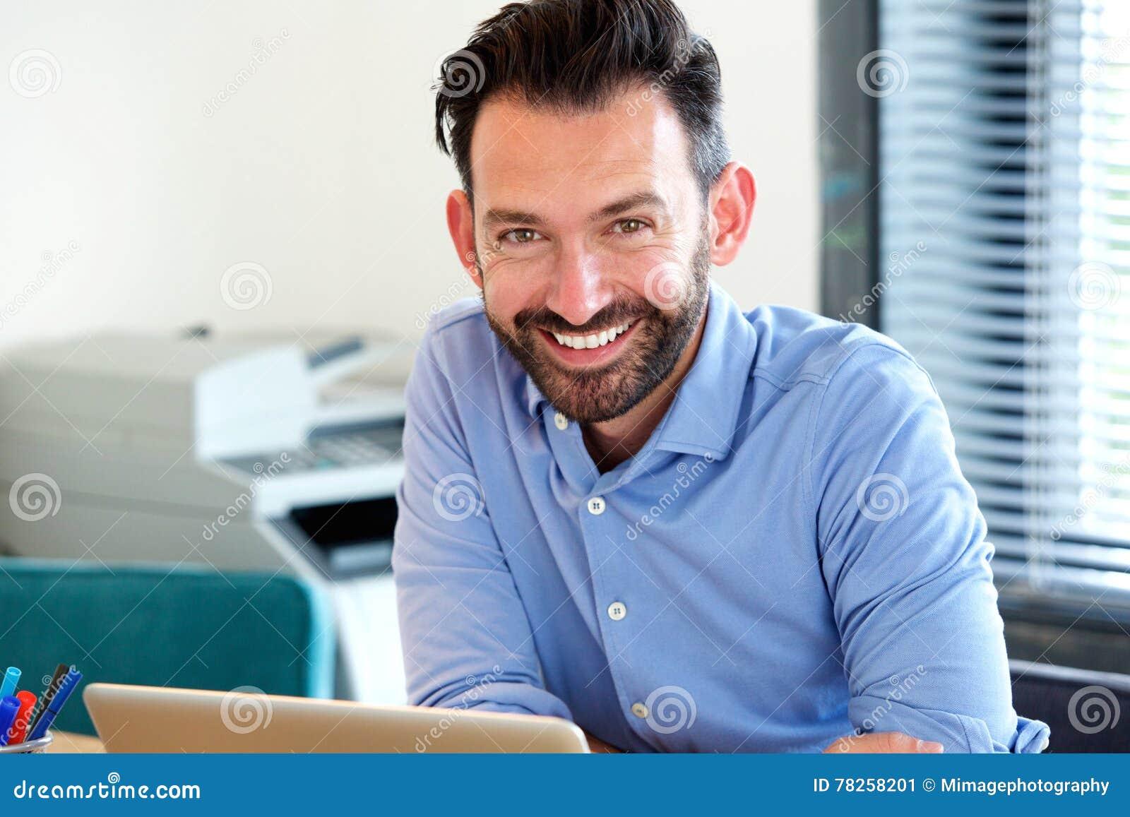 Εύθυμη μέση ηλικίας συνεδρίαση τύπων στο γραφείο του