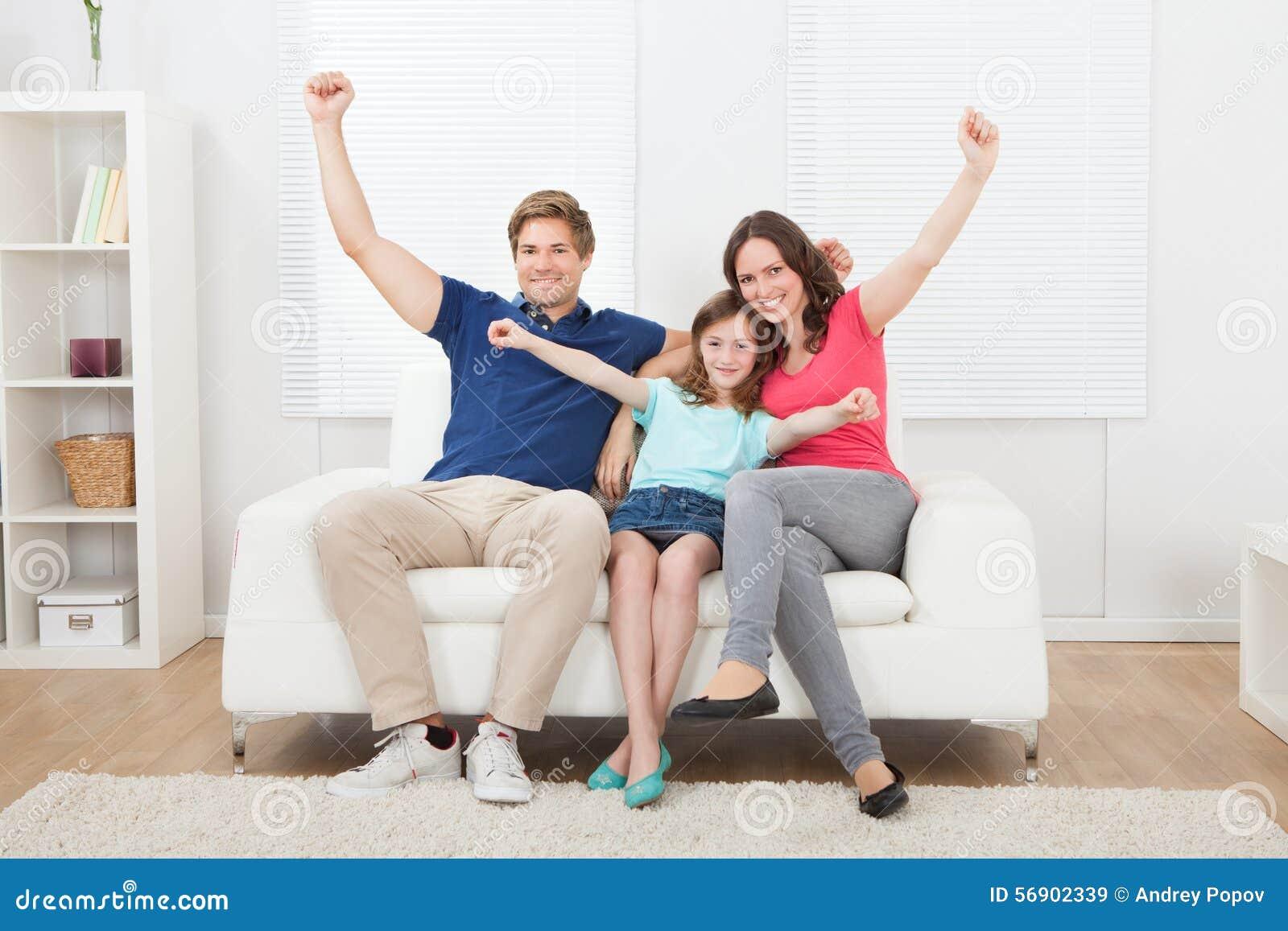 Εύθυμη οικογένεια με αυξημένη την όπλα συνεδρίαση στον καναπέ