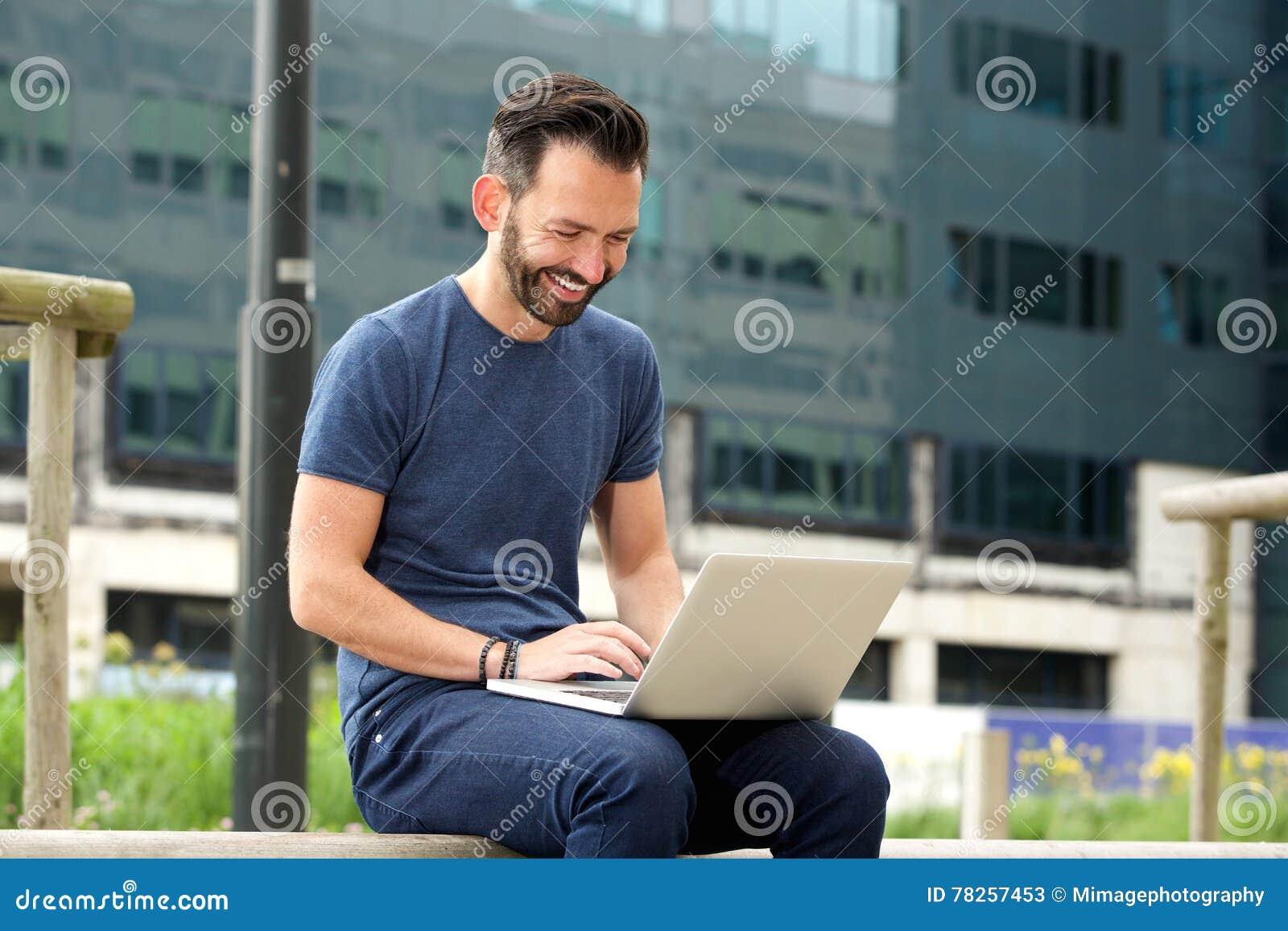 Εύθυμη συνεδρίαση ατόμων υπαίθρια και εργαζόμενος στο lap-top