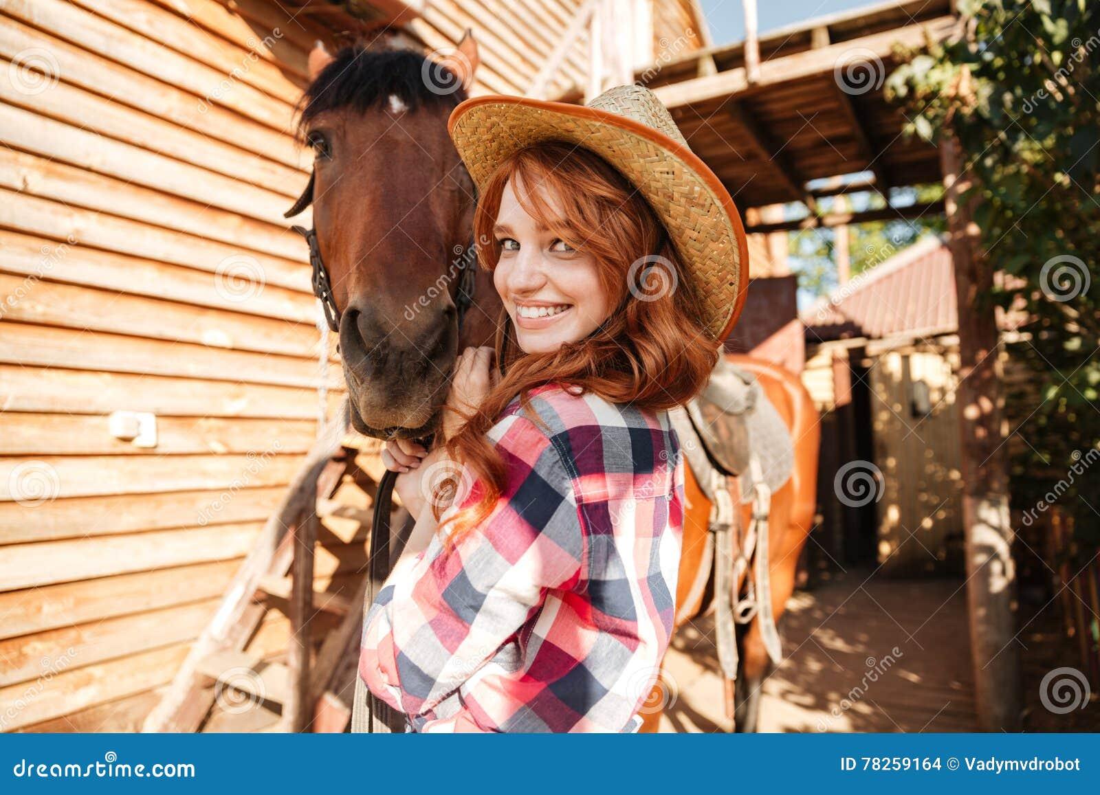 Εύθυμη χαριτωμένη νέα γυναίκα cowgirl στο καπέλο με το άλογο