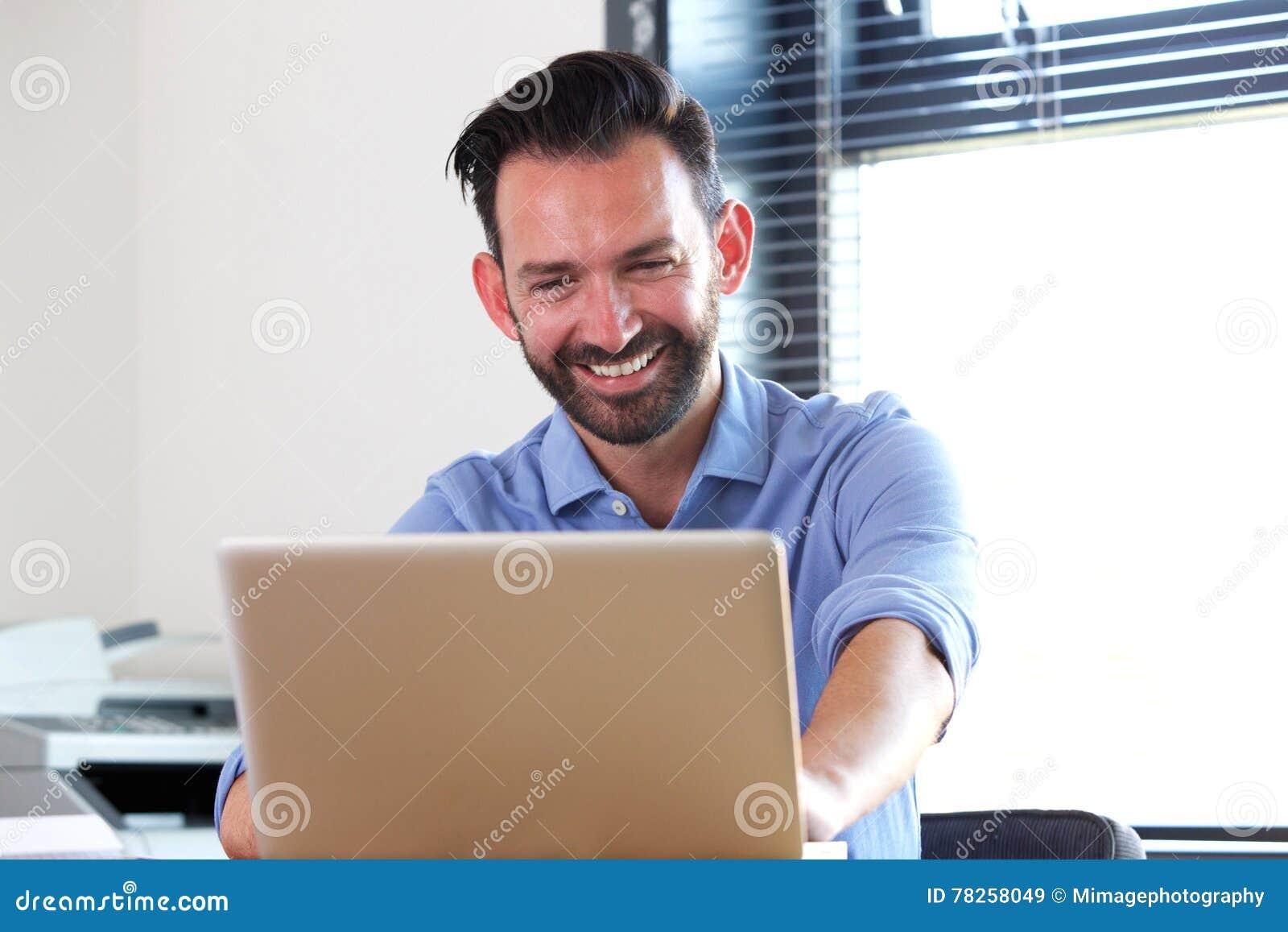 Εύθυμη ώριμη συνεδρίαση ατόμων στο γραφείο του και χρησιμοποίηση του lap-top