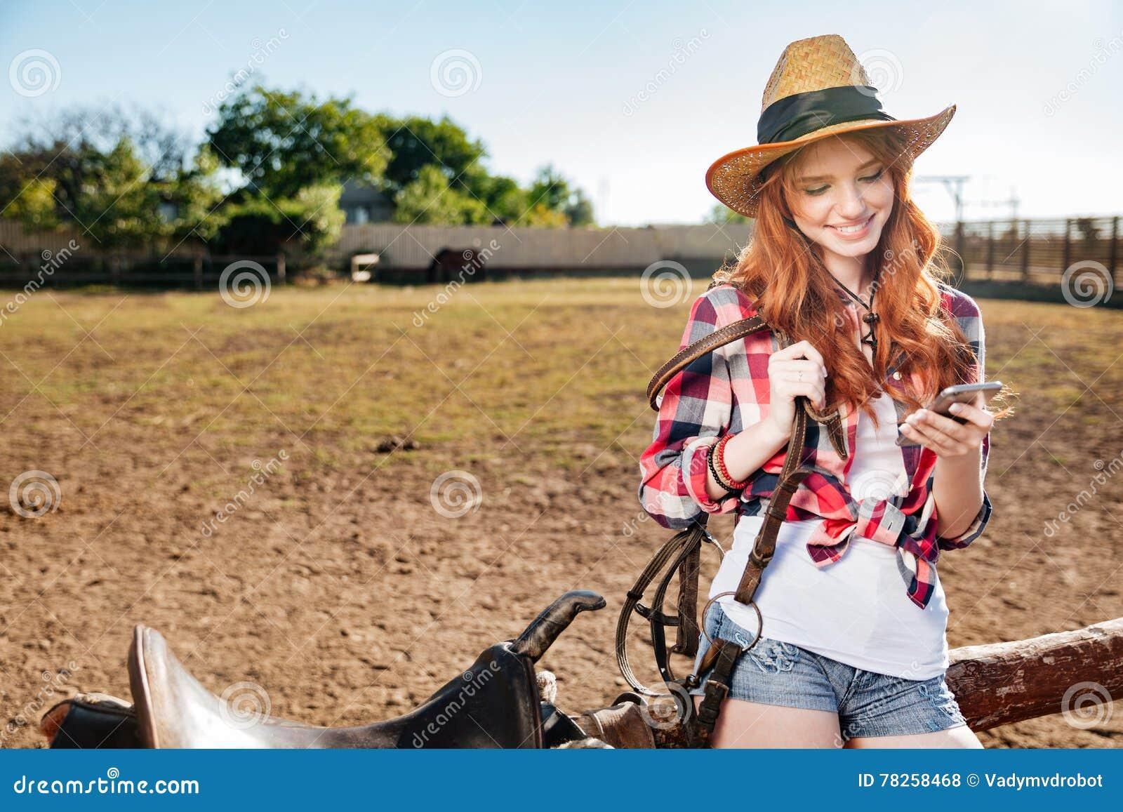 Εύθυμη redhead νέα γυναίκα cowgirl που χρησιμοποιεί το τηλέφωνο κυττάρων στο χωριό