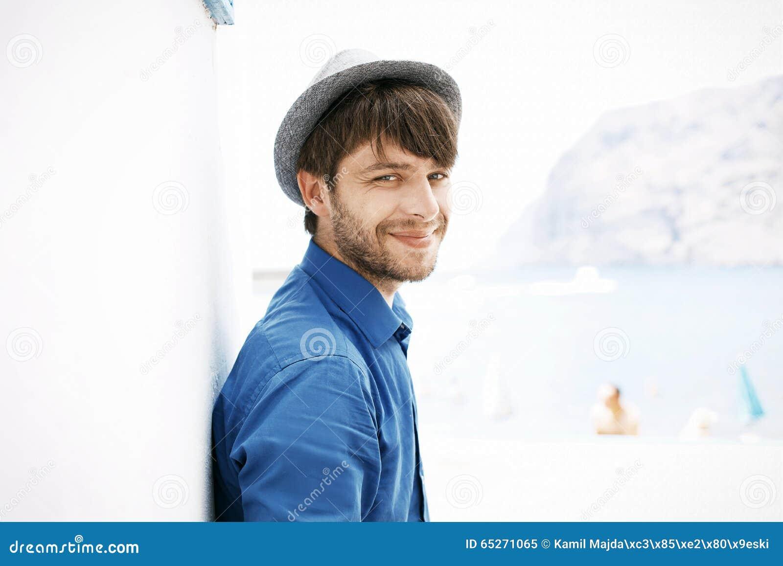 Εύθυμος και όμορφος τύπος με το καθιερώνον τη μόδα καπέλο