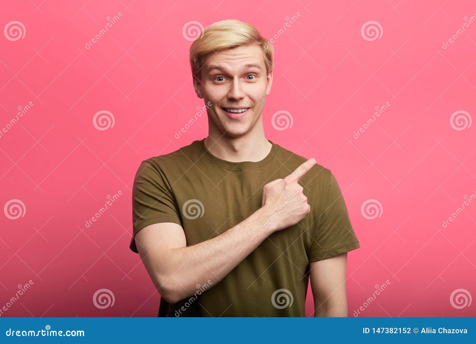 Εύθυμος ξανθομάλλης μοντέρνος τύπος που δείχνει το δάχτυλο κάπου