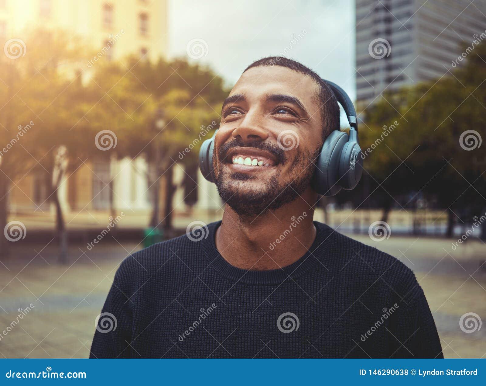 Εύθυμο άτομο που απολαμβάνει τη μουσική στο ασύρματο ακουστικό