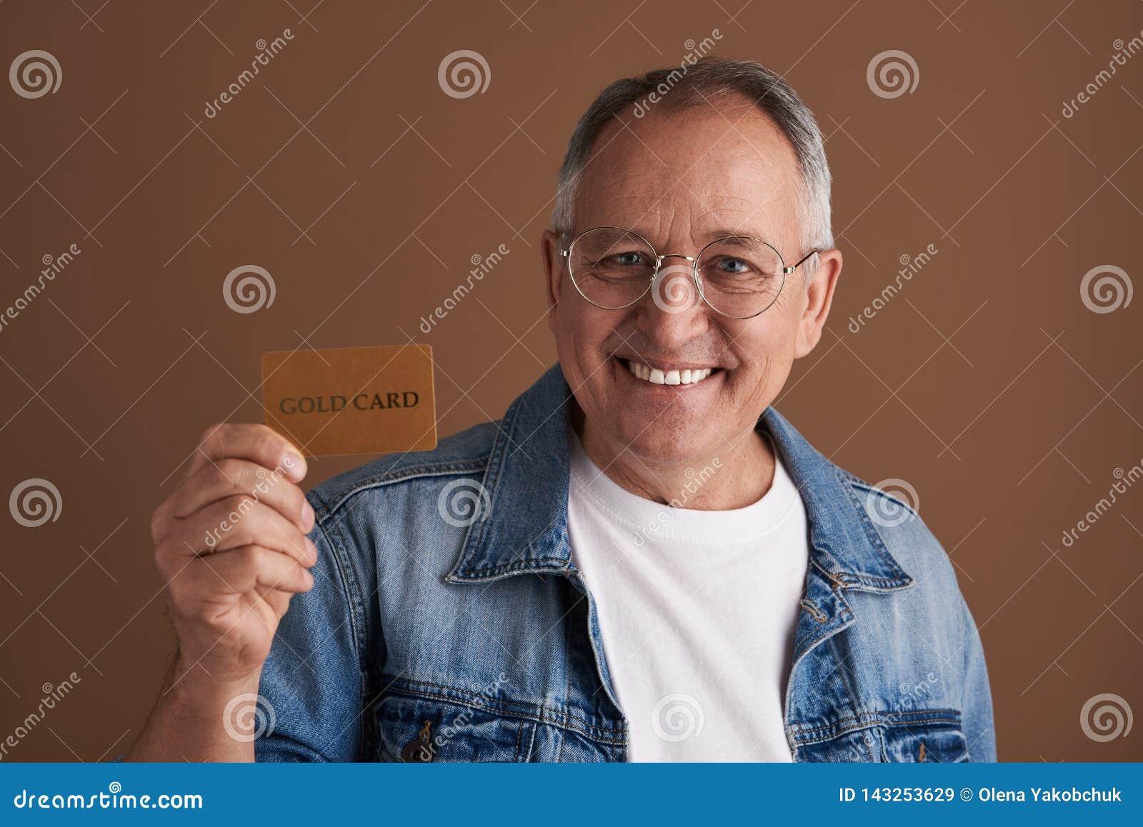 Εύθυμο άτομο που είναι υπερήφανο της χρυσών κάρτας και του χαμόγελού του