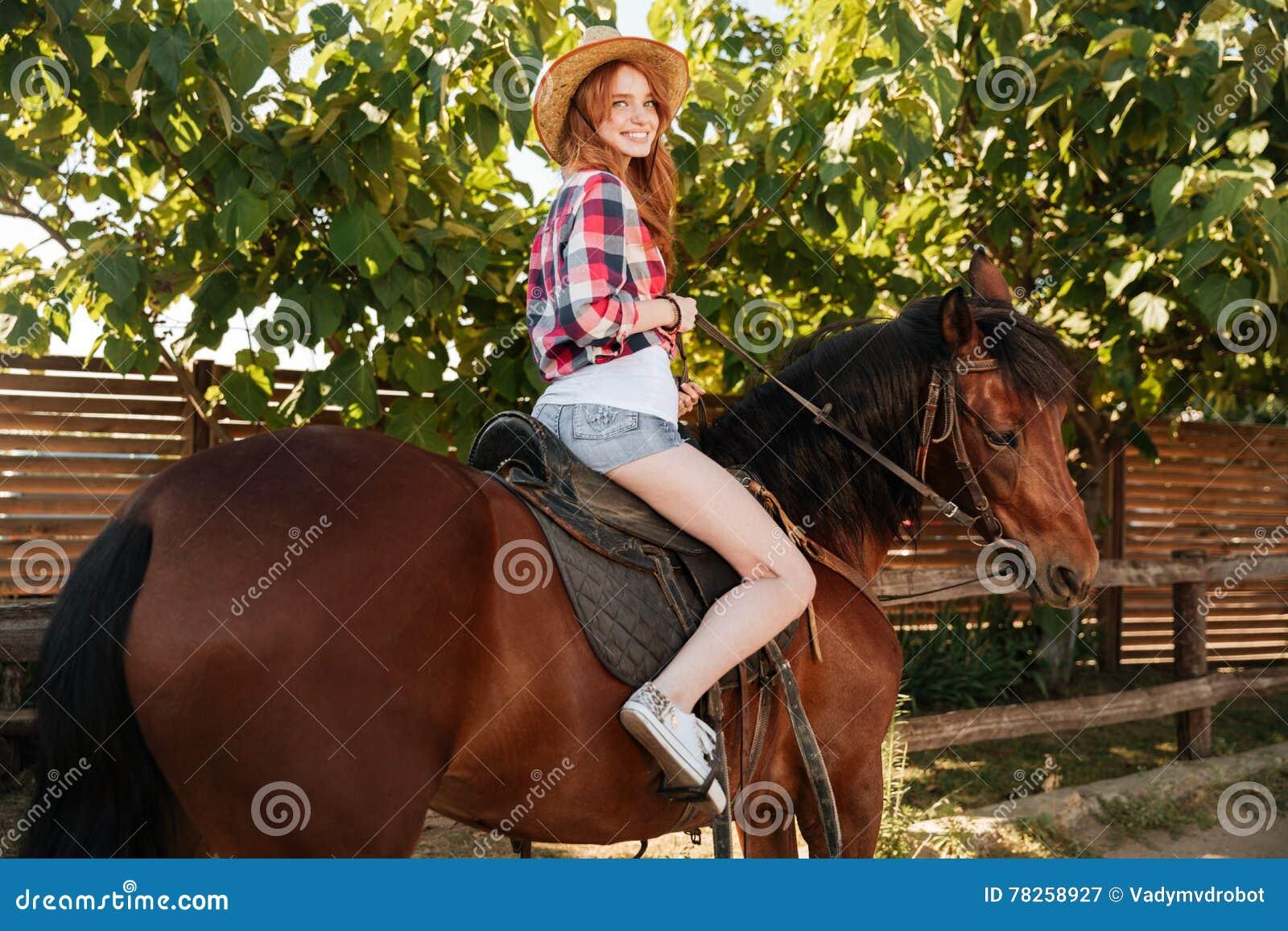 Εύθυμο άλογο οδήγησης γυναικών cowgirl στο αγρόκτημα