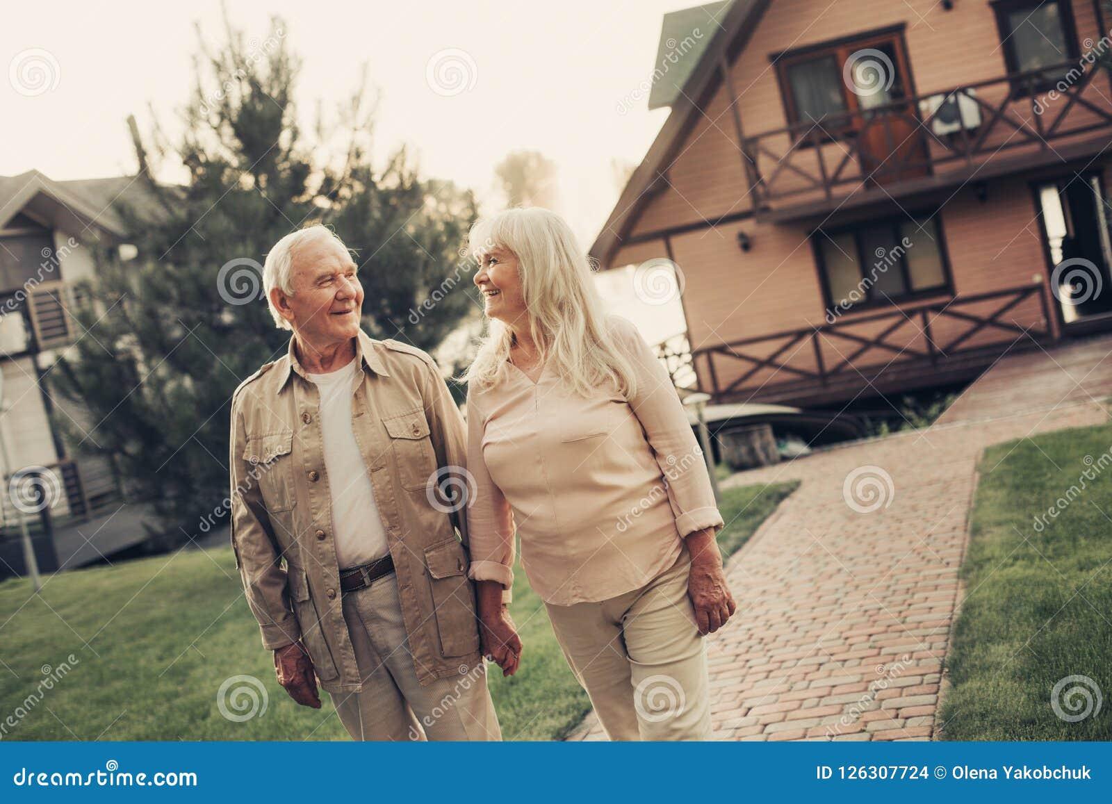 Εύθυμο γκρίζο μαλλιαρό ζευγάρι χαμόγελου που αντιμετωπίζει το σπίτι