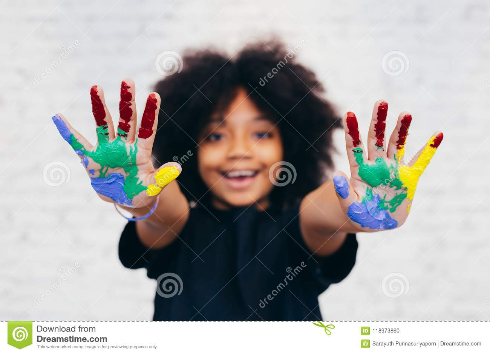 Εύθυμο και δημιουργικό παιδί αφροαμερικάνων που παίρνει τα χέρια βρώμικα με πολλά χρώματα